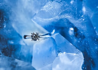 silver-colored ring with clear gemstone inside ice