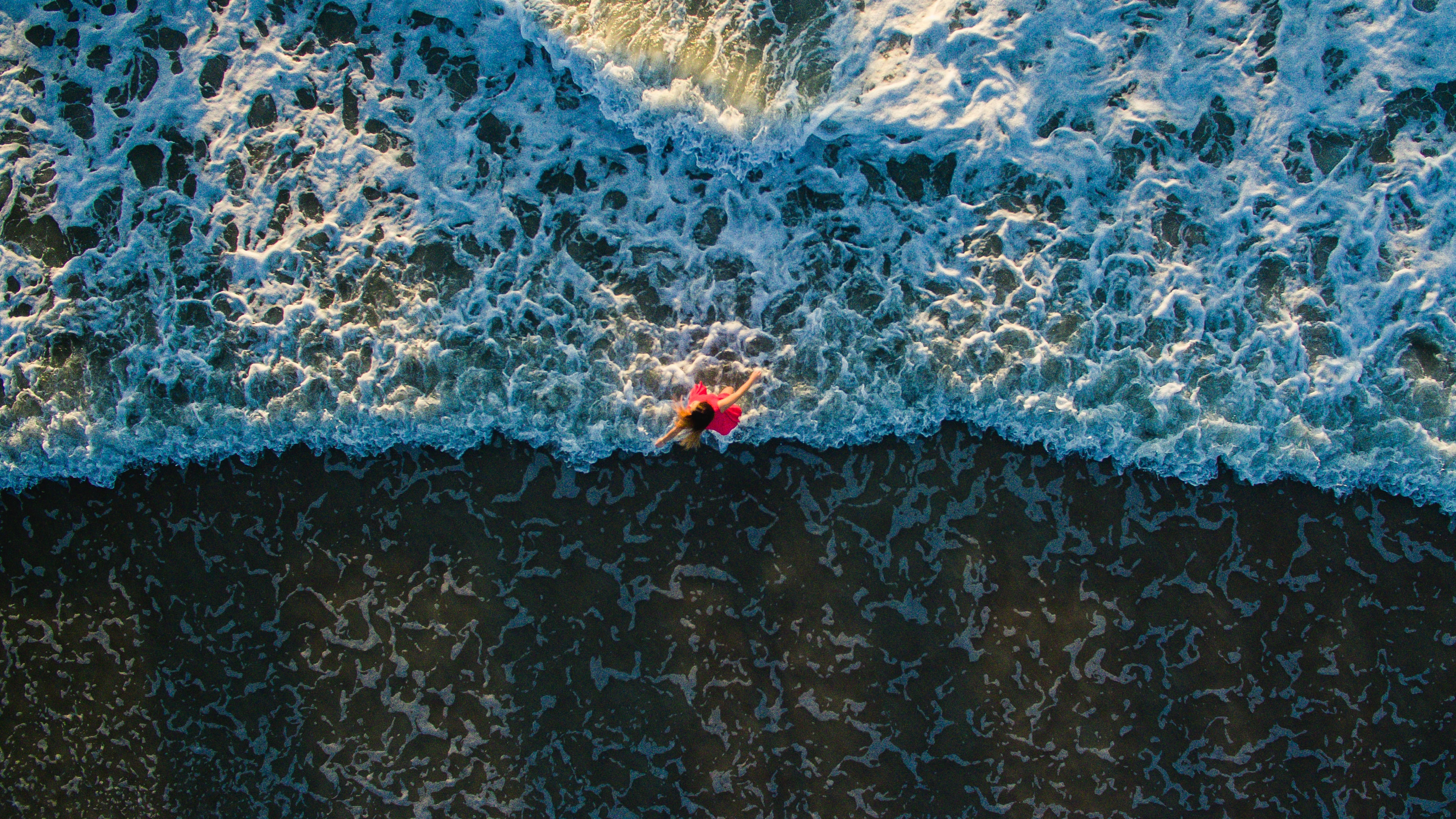 Top view of a woman in a red dress playing in the ocean waves of Jacksonville beach