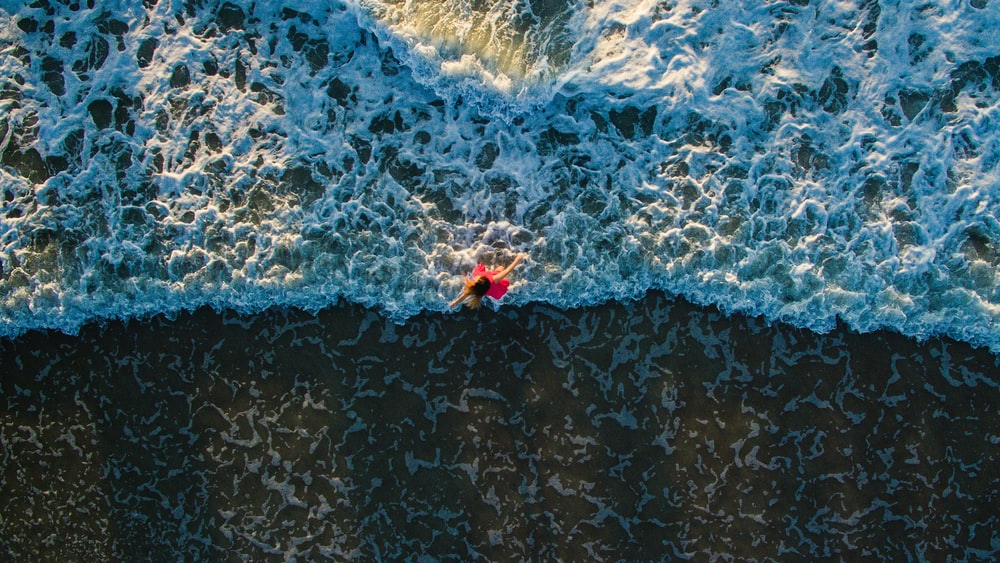aerial photo of woman standing on shore