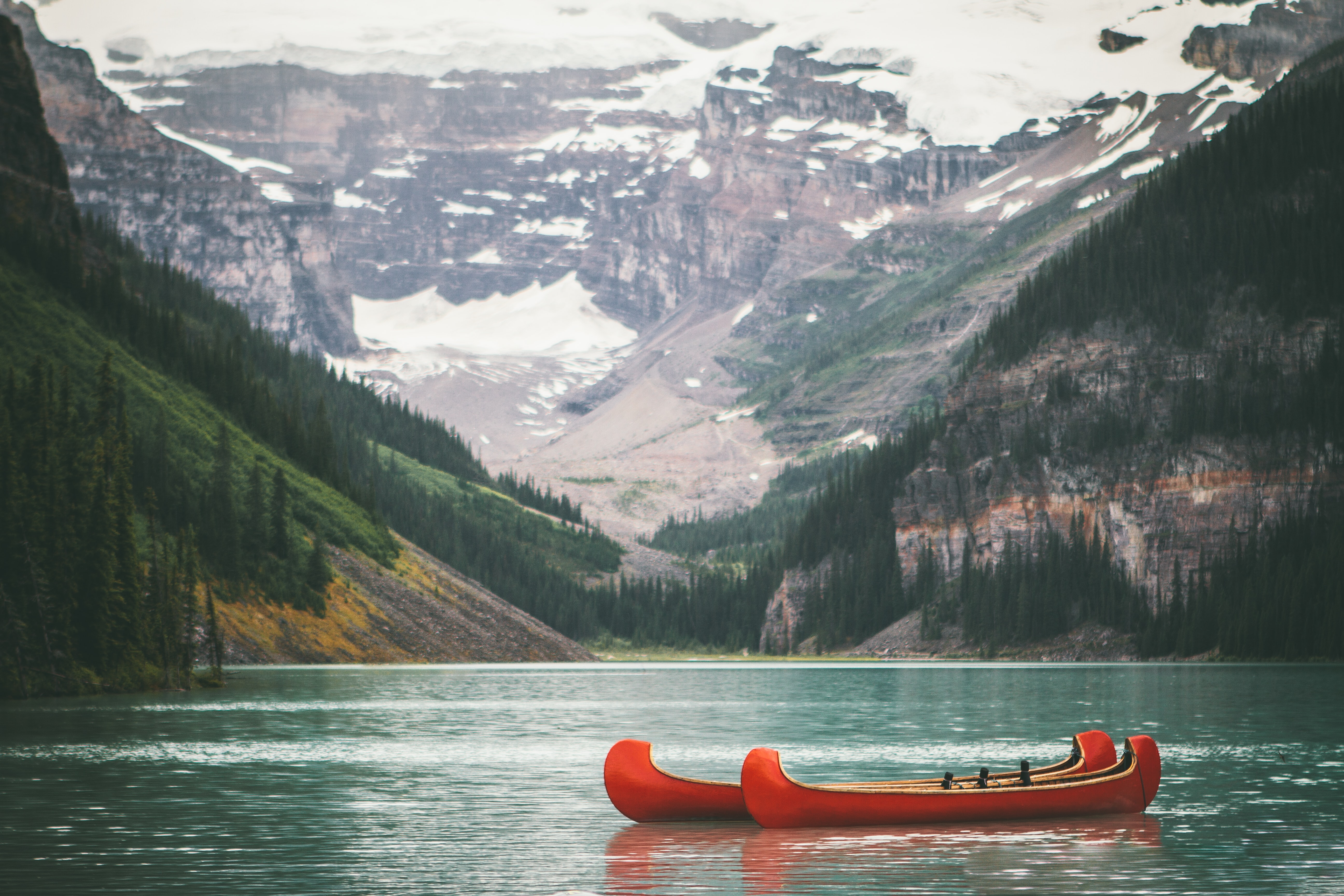 two orange boats on body of water in front of mountain with trees during daytime