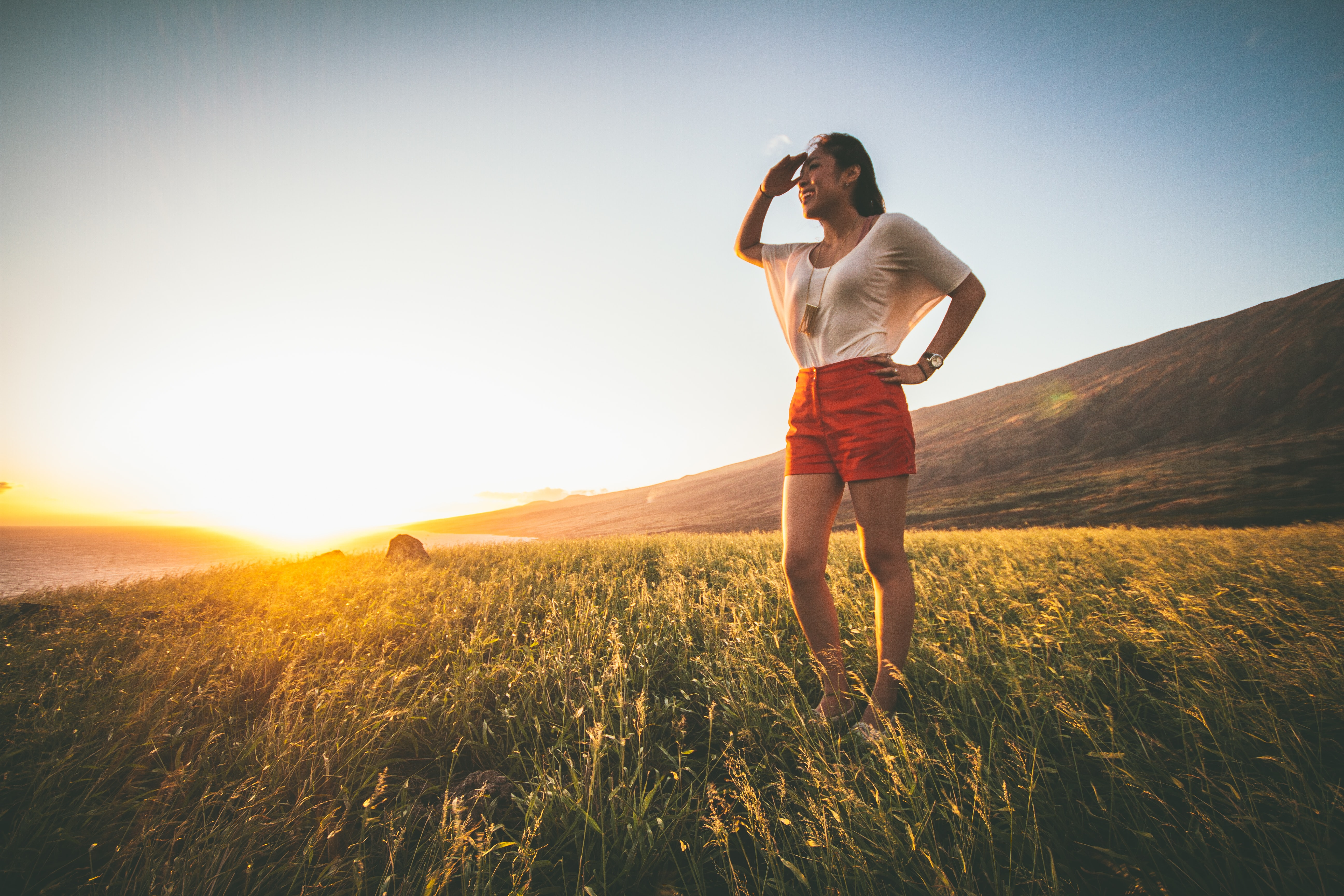 woman in beige batwing sleeved shirt and red shorts standing on grass field