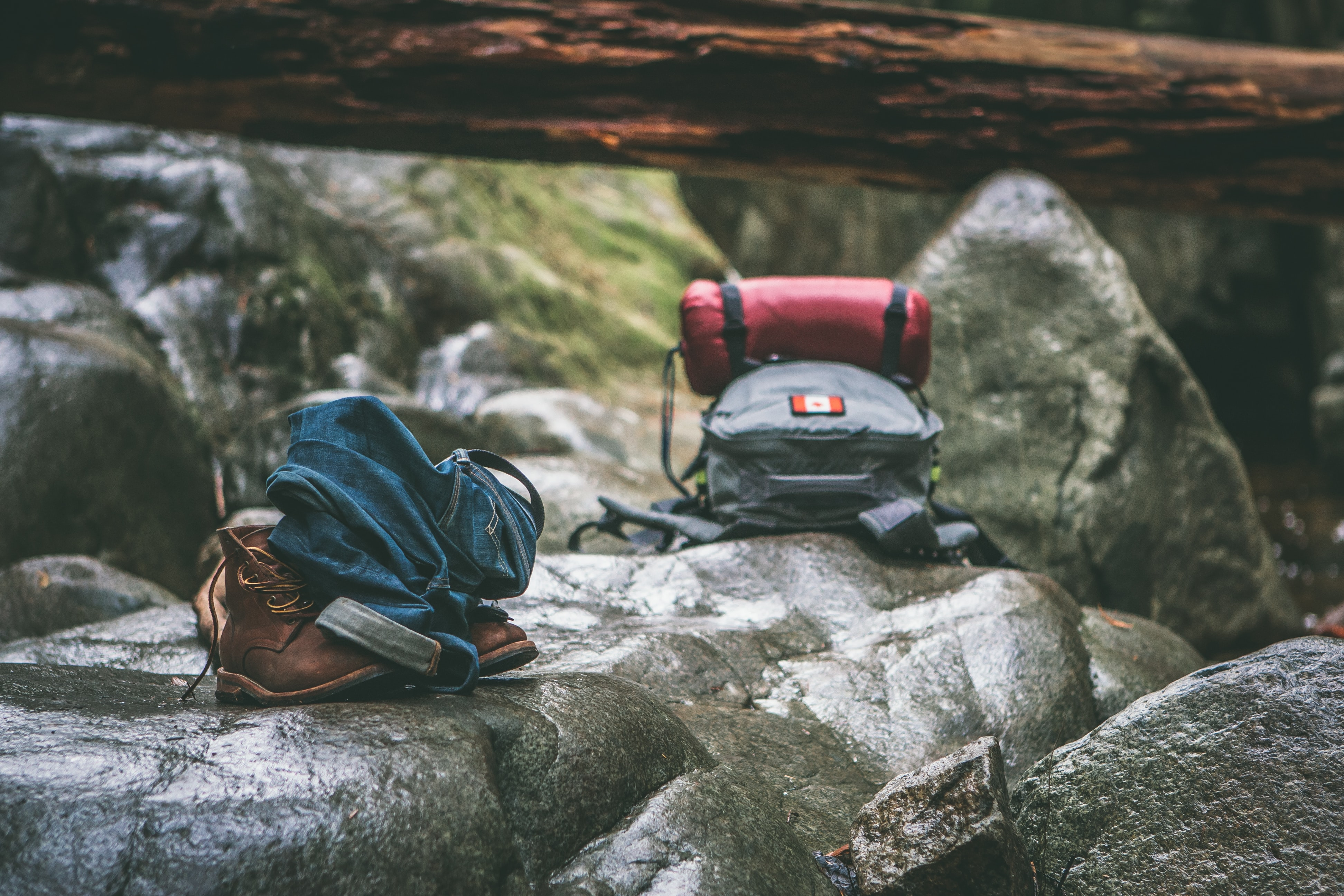 A backpack, sleeping bag, jeans, belt, and hiking boots on a rock in Cypress Falls Park