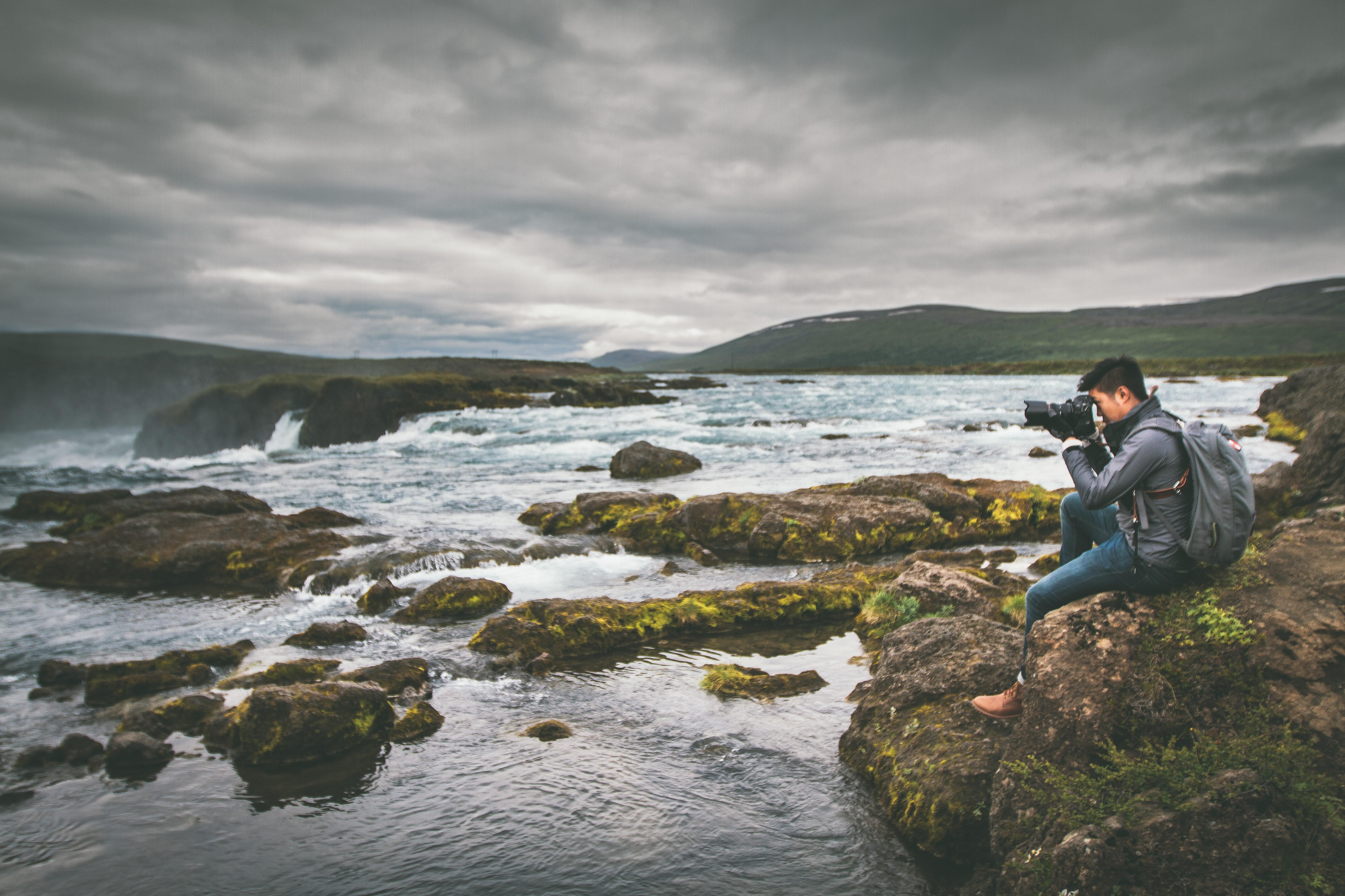A man sits on a rock near the water to take a picture of the Góðafoss Waterfall