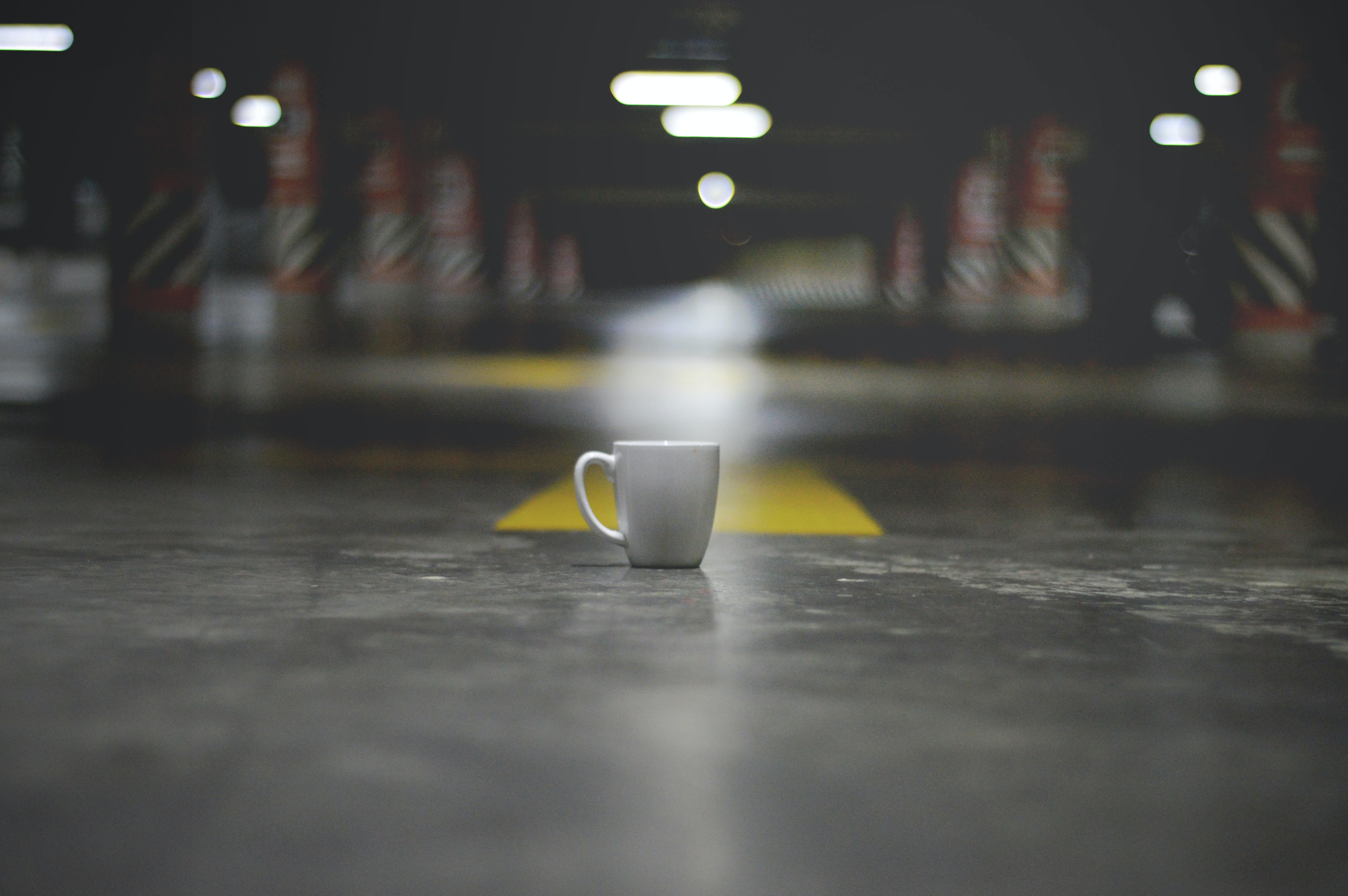 A coffee mug in a garage parking lot