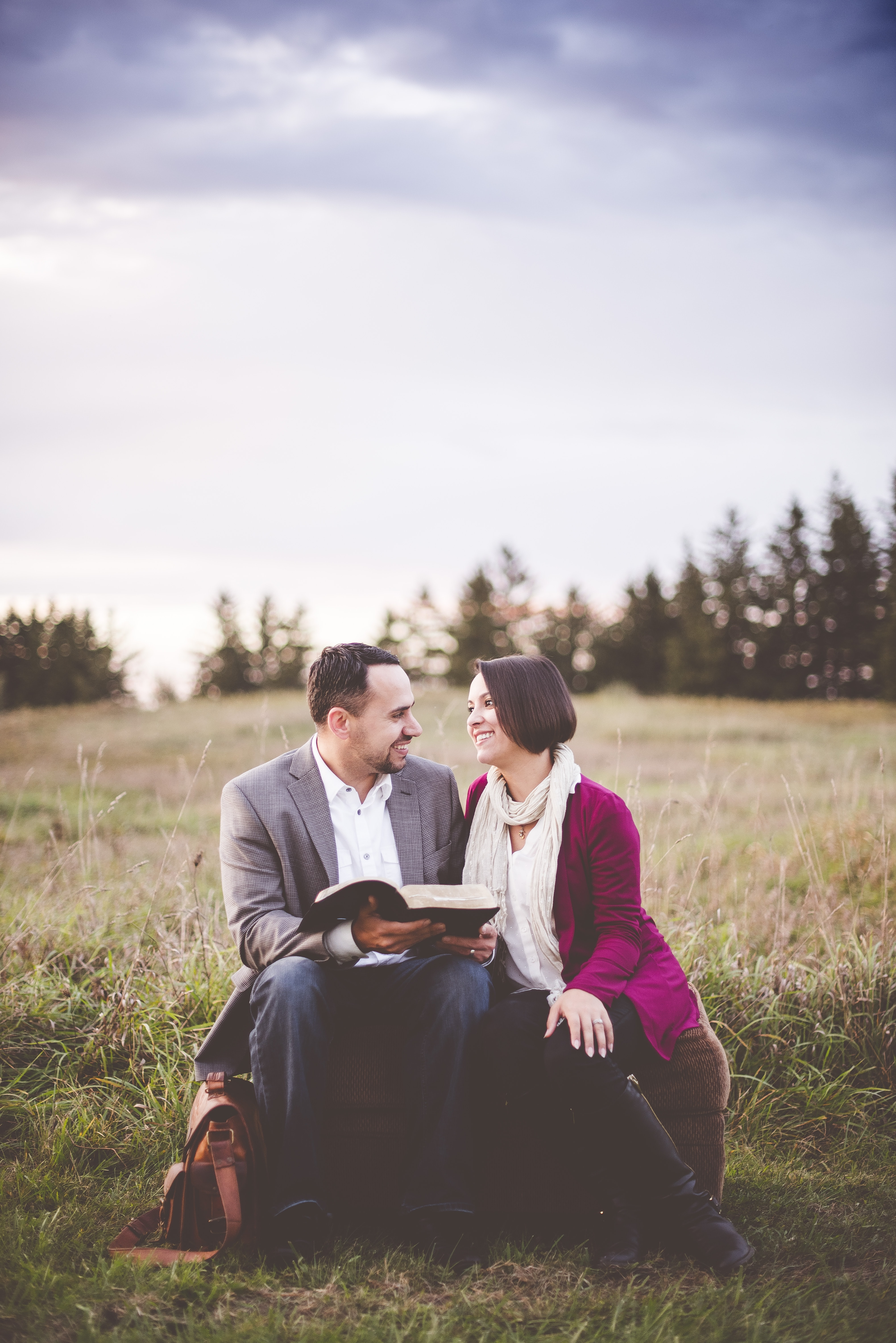 A married couple sits looking at each other on an ottoman outdoors. He's holding a book
