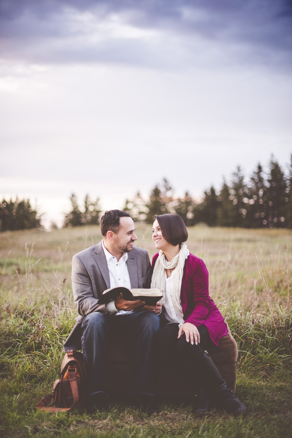 photo of man reading book to woman under grey cloudy sky