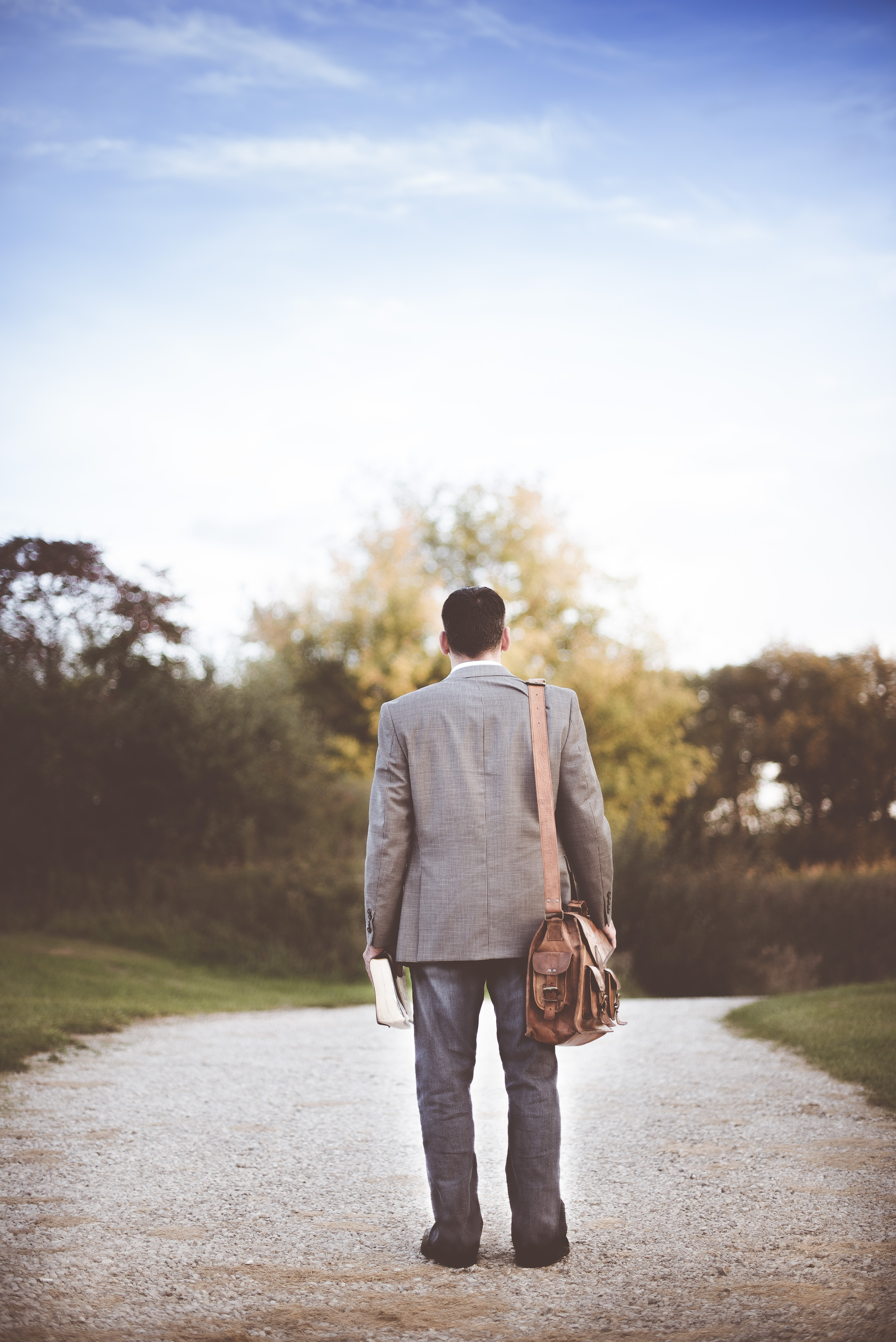 A man in a suit with a leather bag on his arm and a thick book in his hand on a dirt path