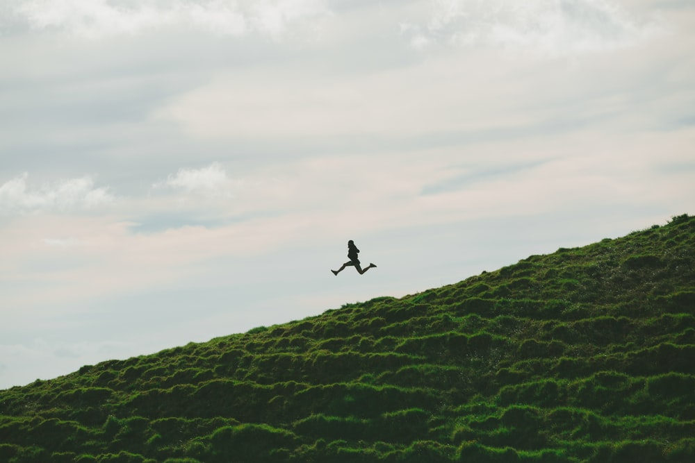 person jumping on grass field under cloudy sky during daytime