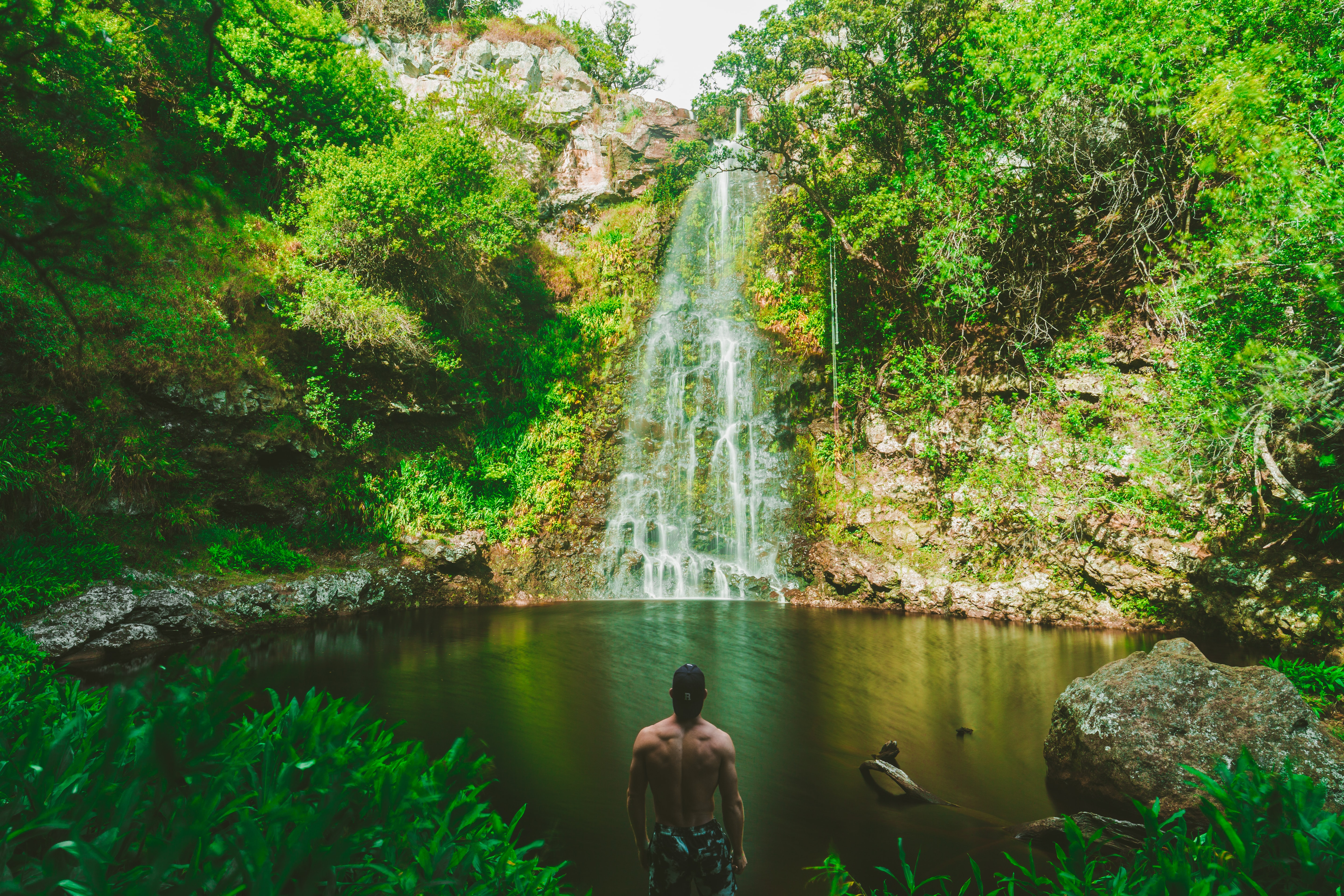 man standing in front of waterfalls during day time