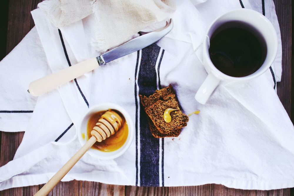 flat lay photography of white knife, honey dipper on bowl, and coffee mug