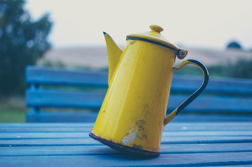 yellow kettle on gray wooden table