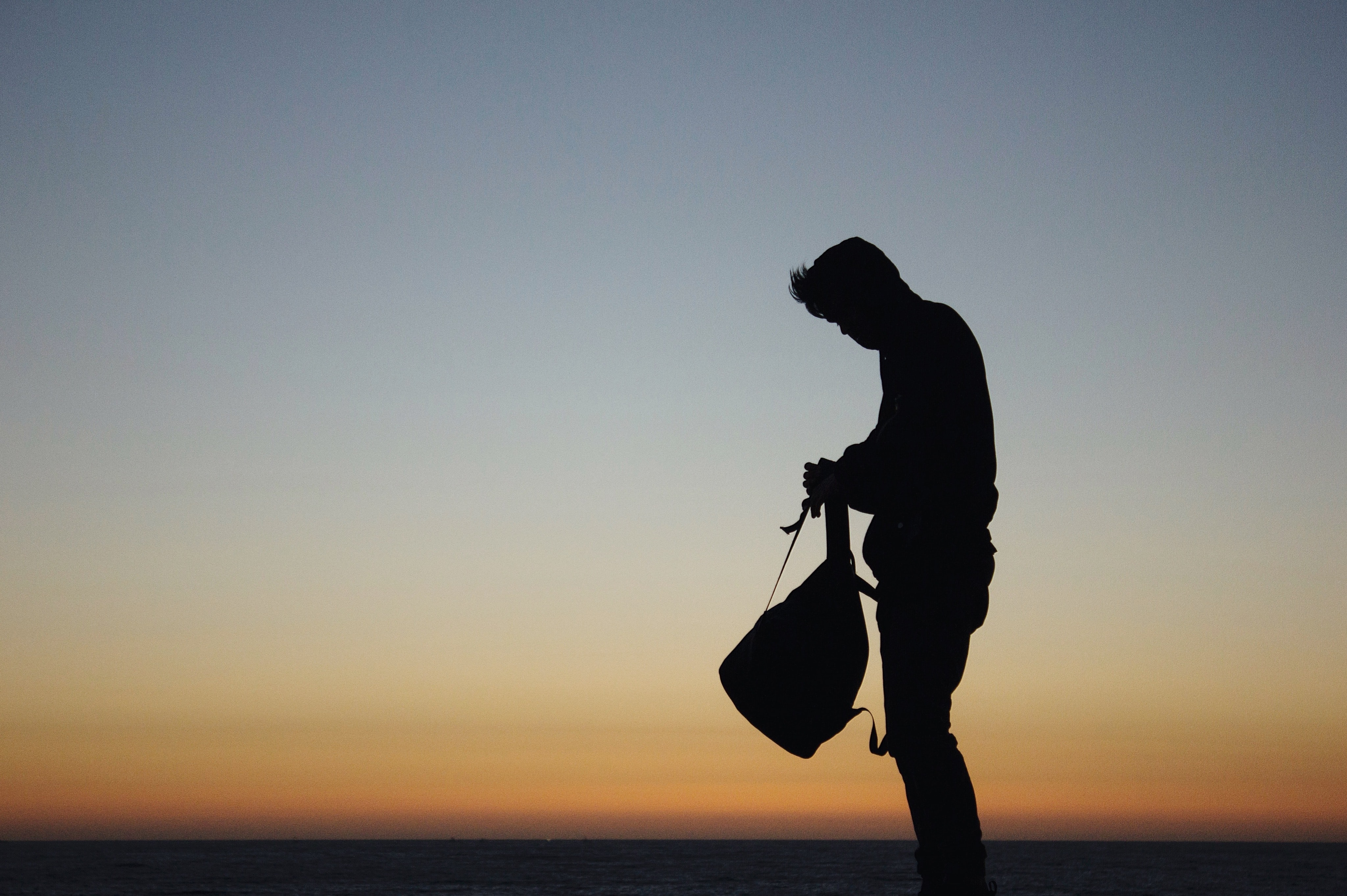Silhouette of a man adjusting a backpack in front of a horizon sunset