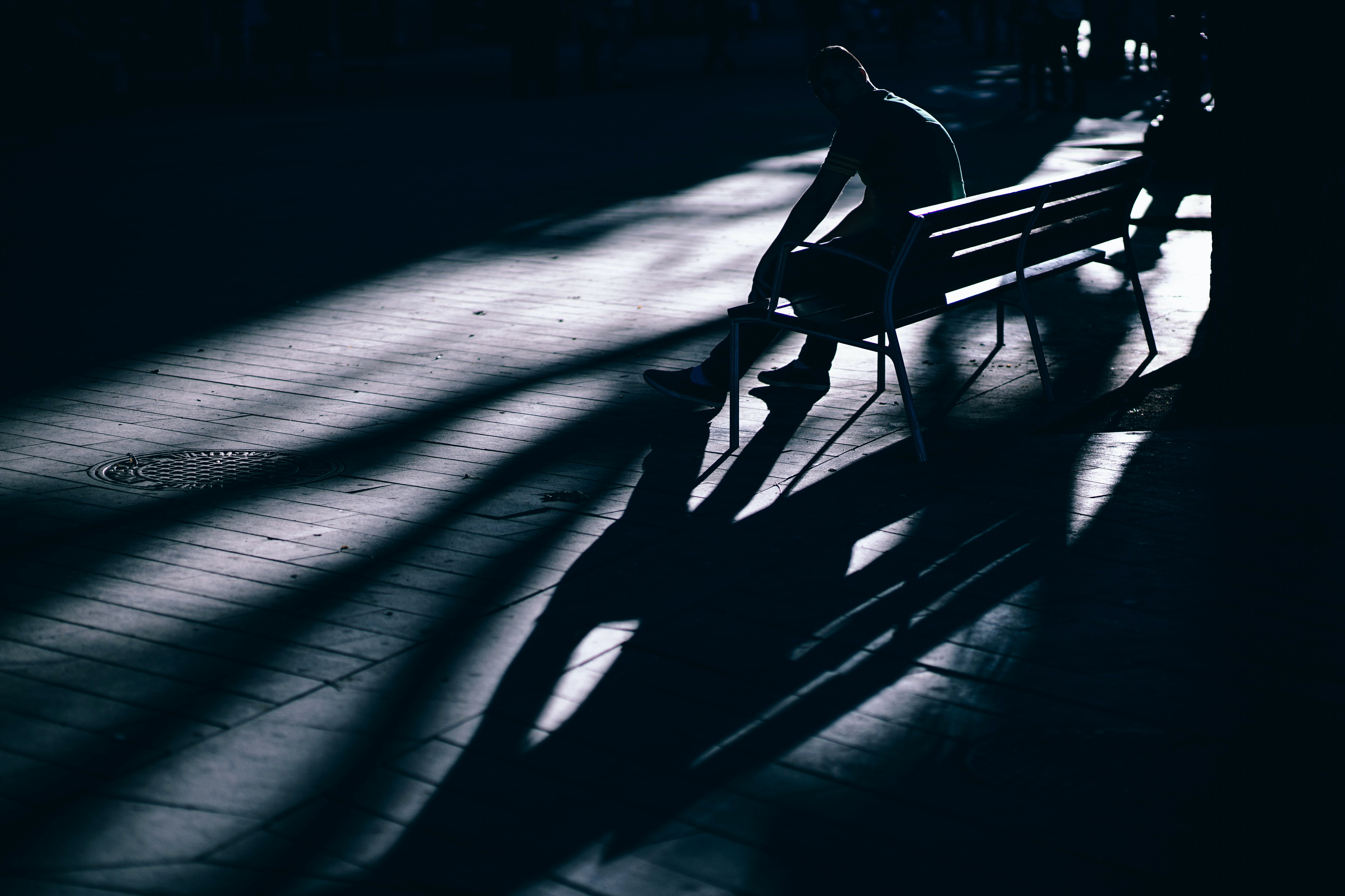 A dim shot of a person sitting on a bench and casting a long shadow