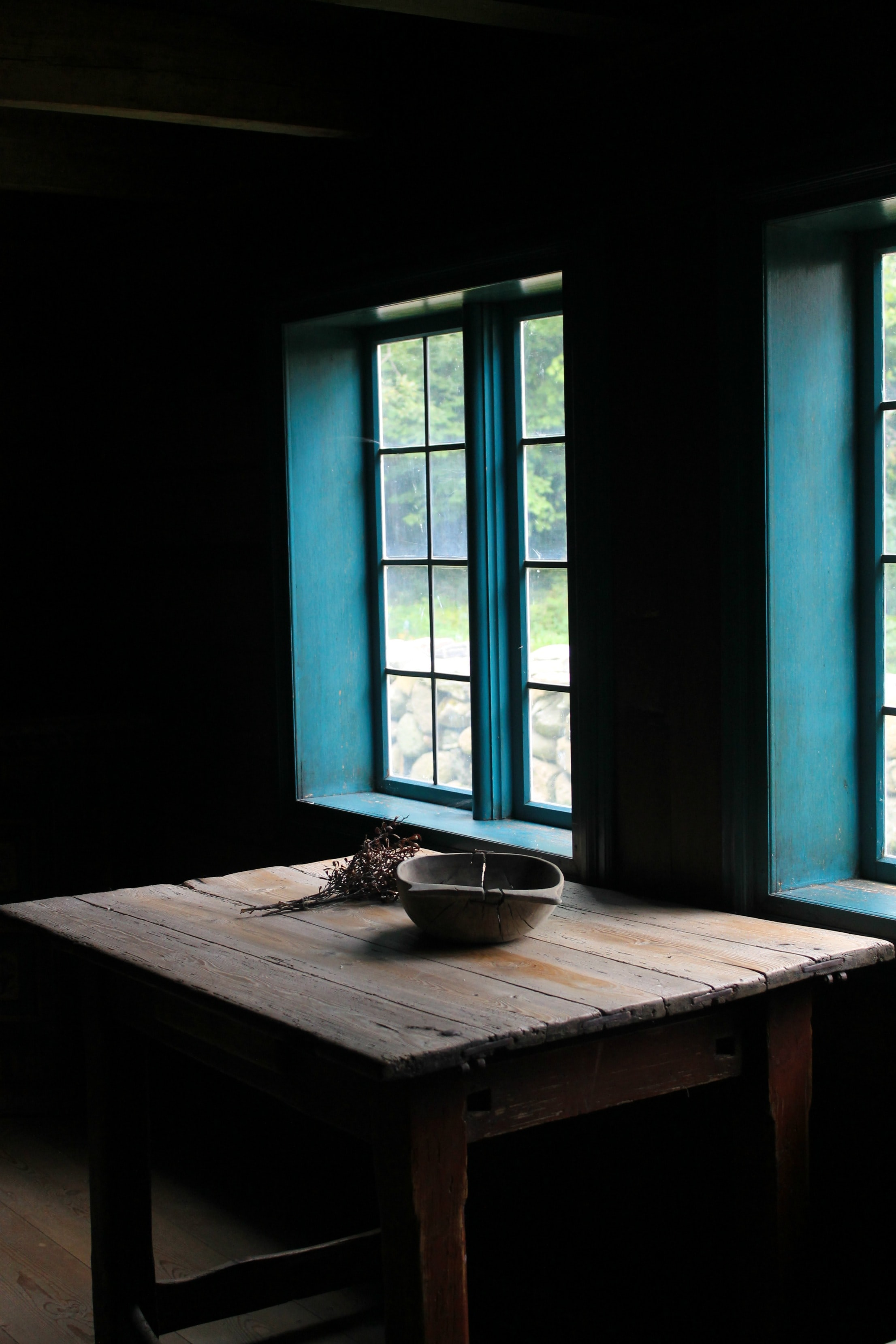 A wooden table with a bowl on it near a window in Folkemuseet