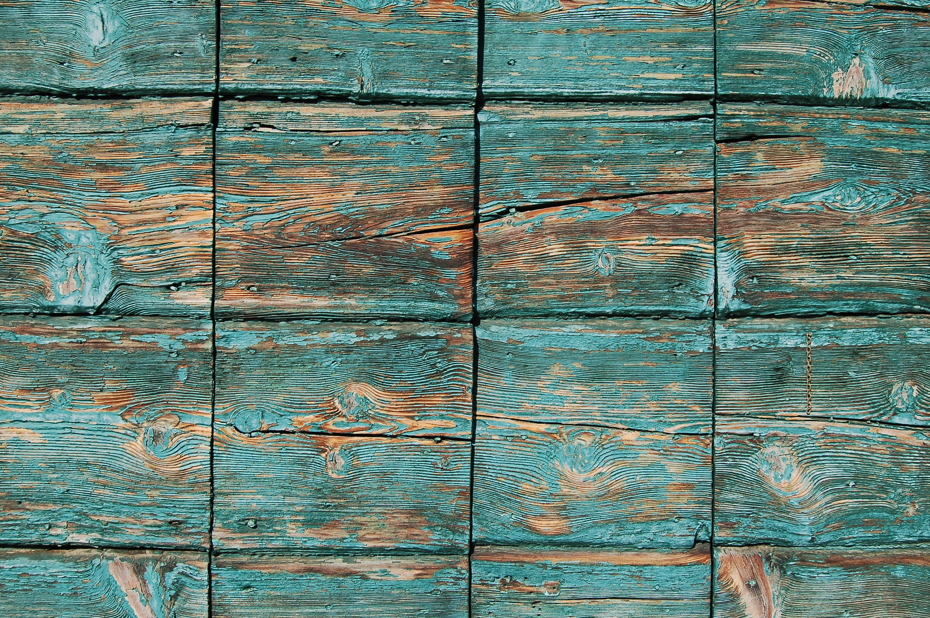 Turquoise paint coming off square wooden planks