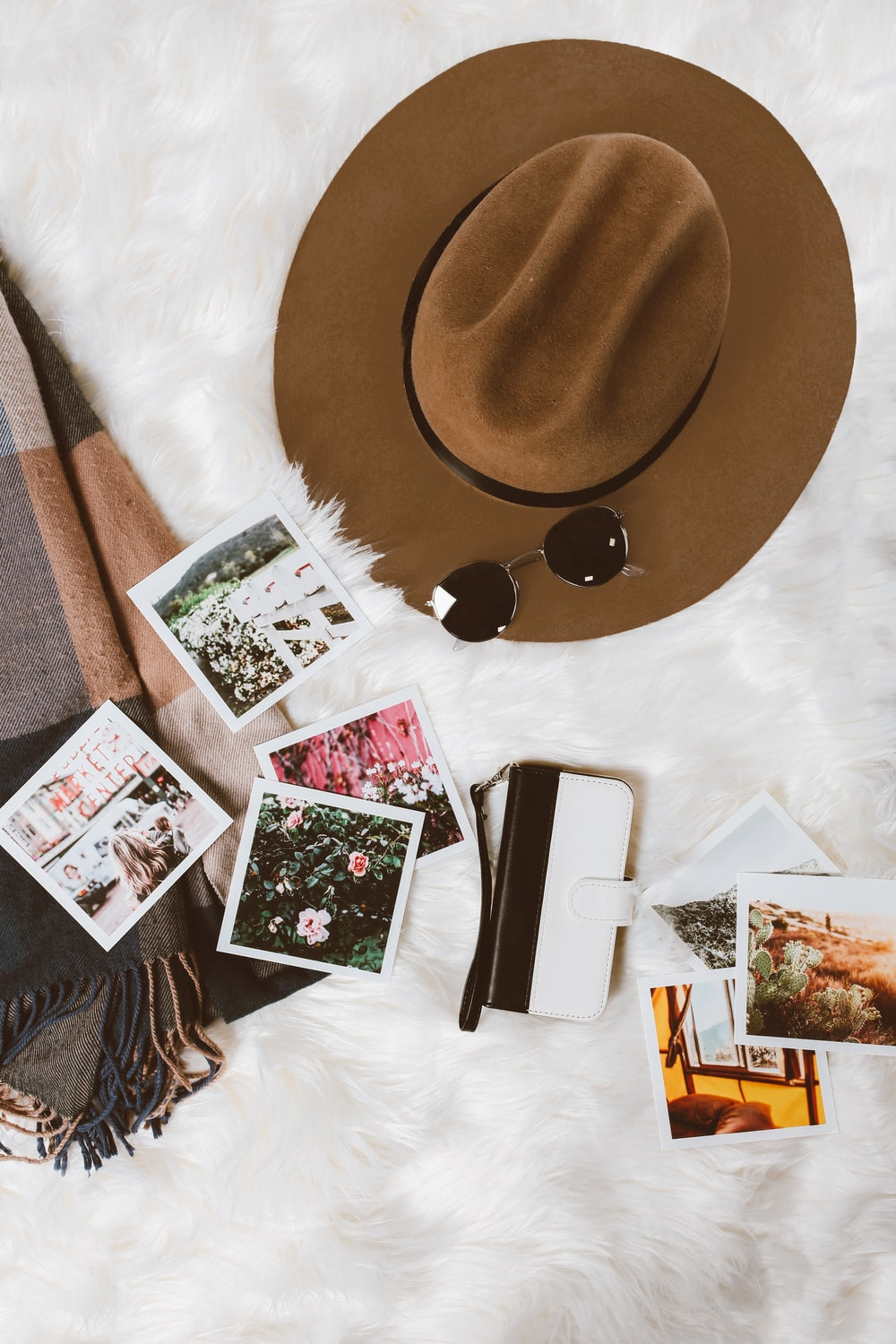 gold-colored framed sunglasses on brown hat beside white and black leather wristlet surrounded by photos on white and gray floral textile