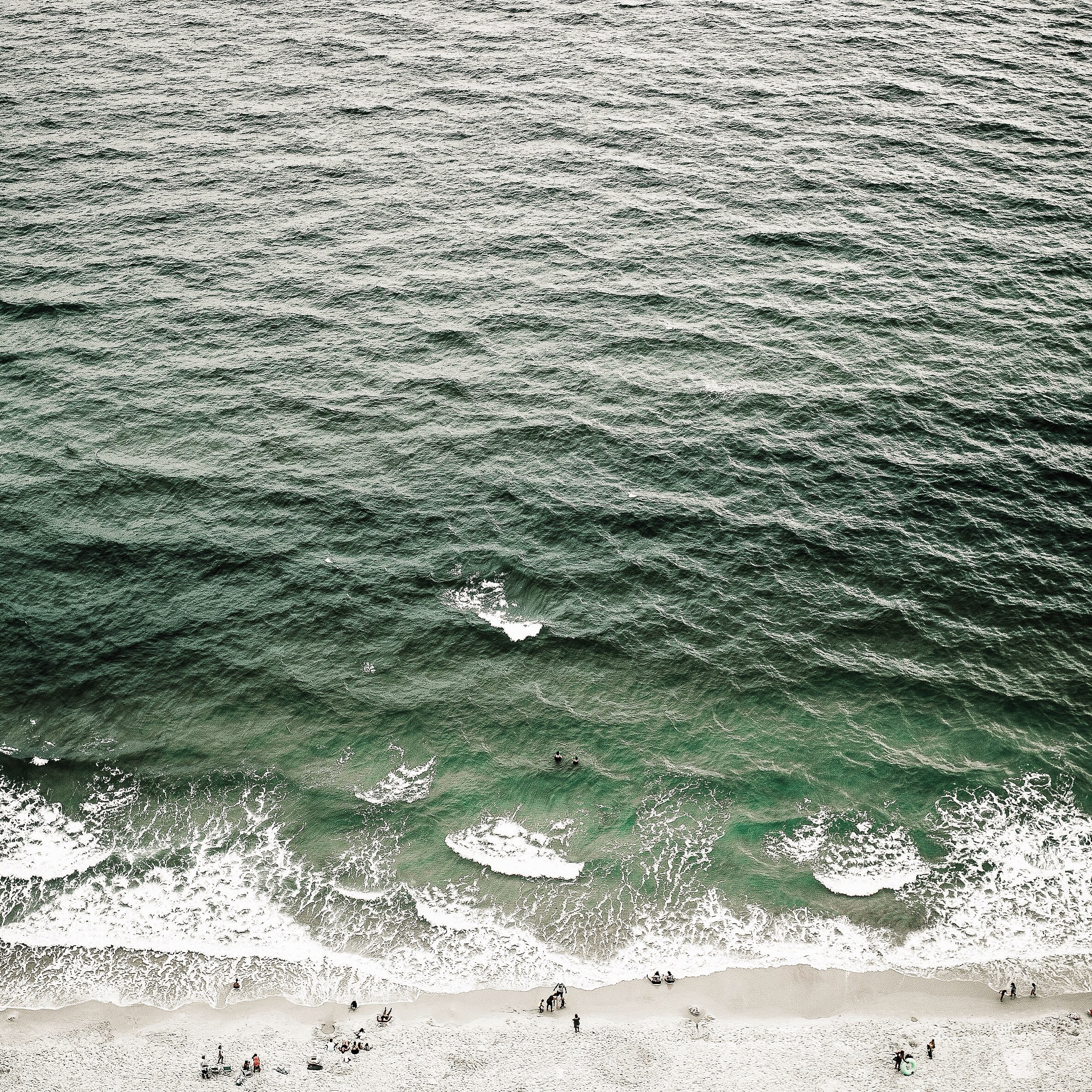Drone aerial view of the ocean waves washing on the sand Gulf Shores