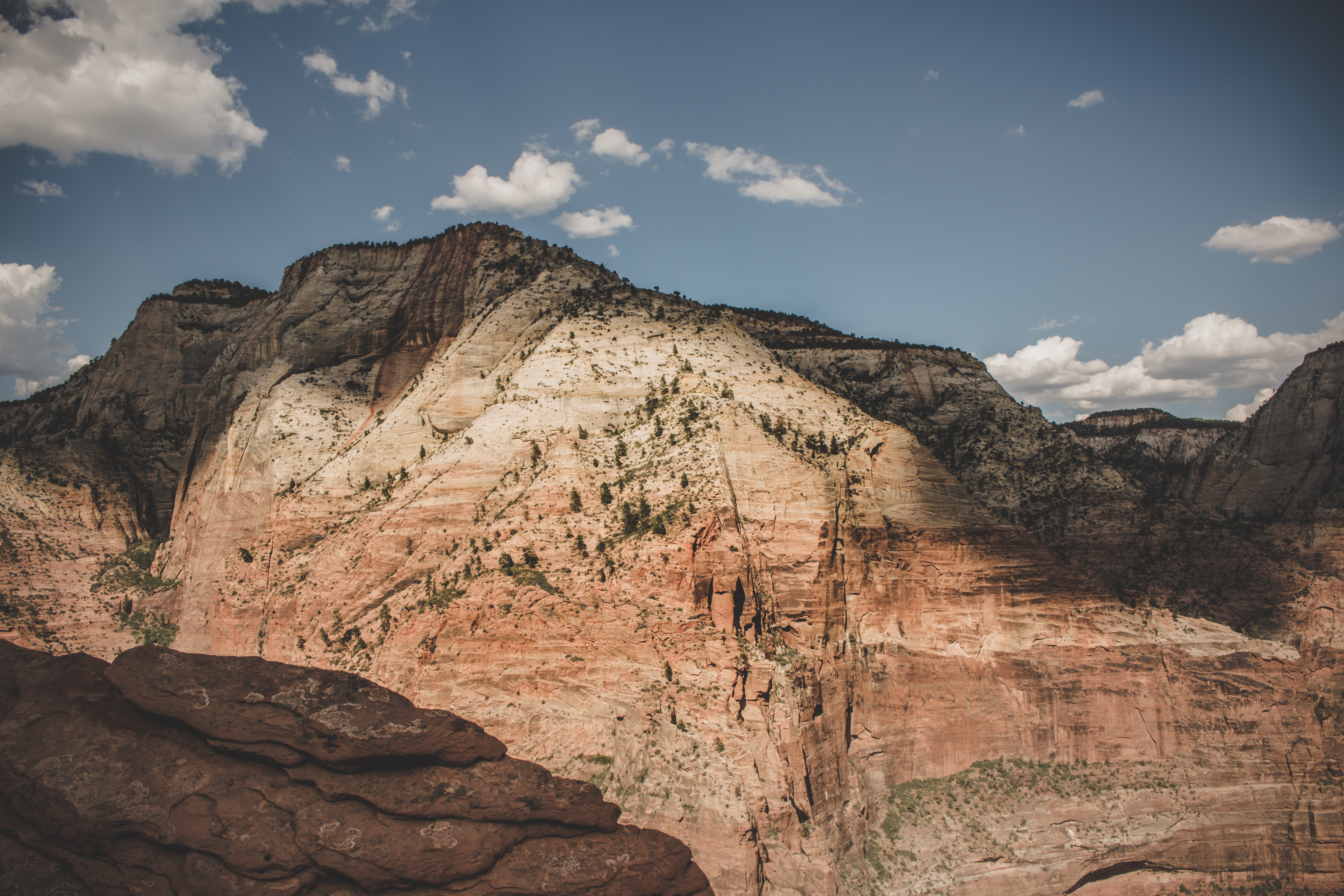 A red sandstone mountain under scattered clouds on a blue sky