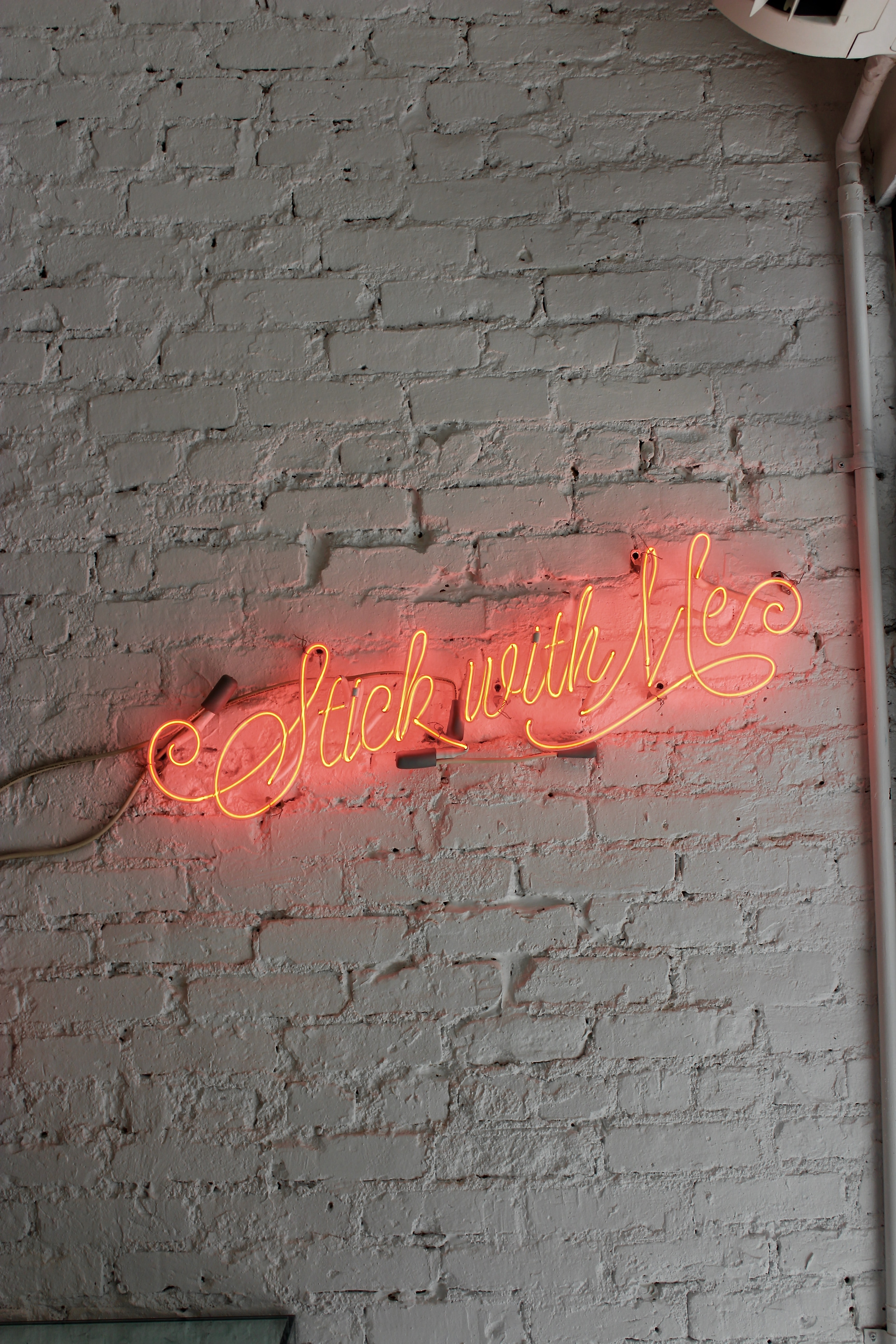 "A red neon with ""stick with me"" written in cursive on a white brick wall"