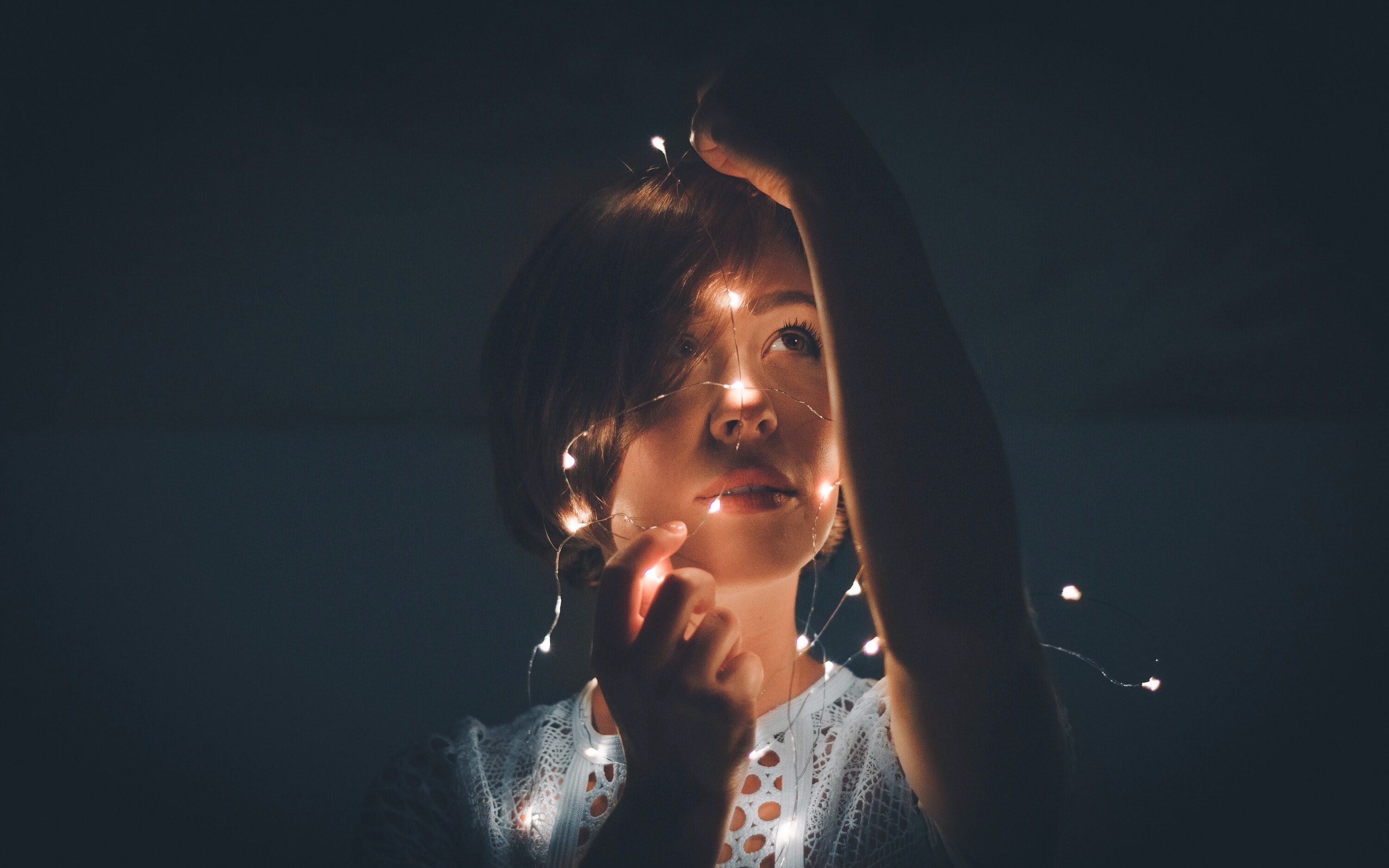 woman holding light string in a dark room