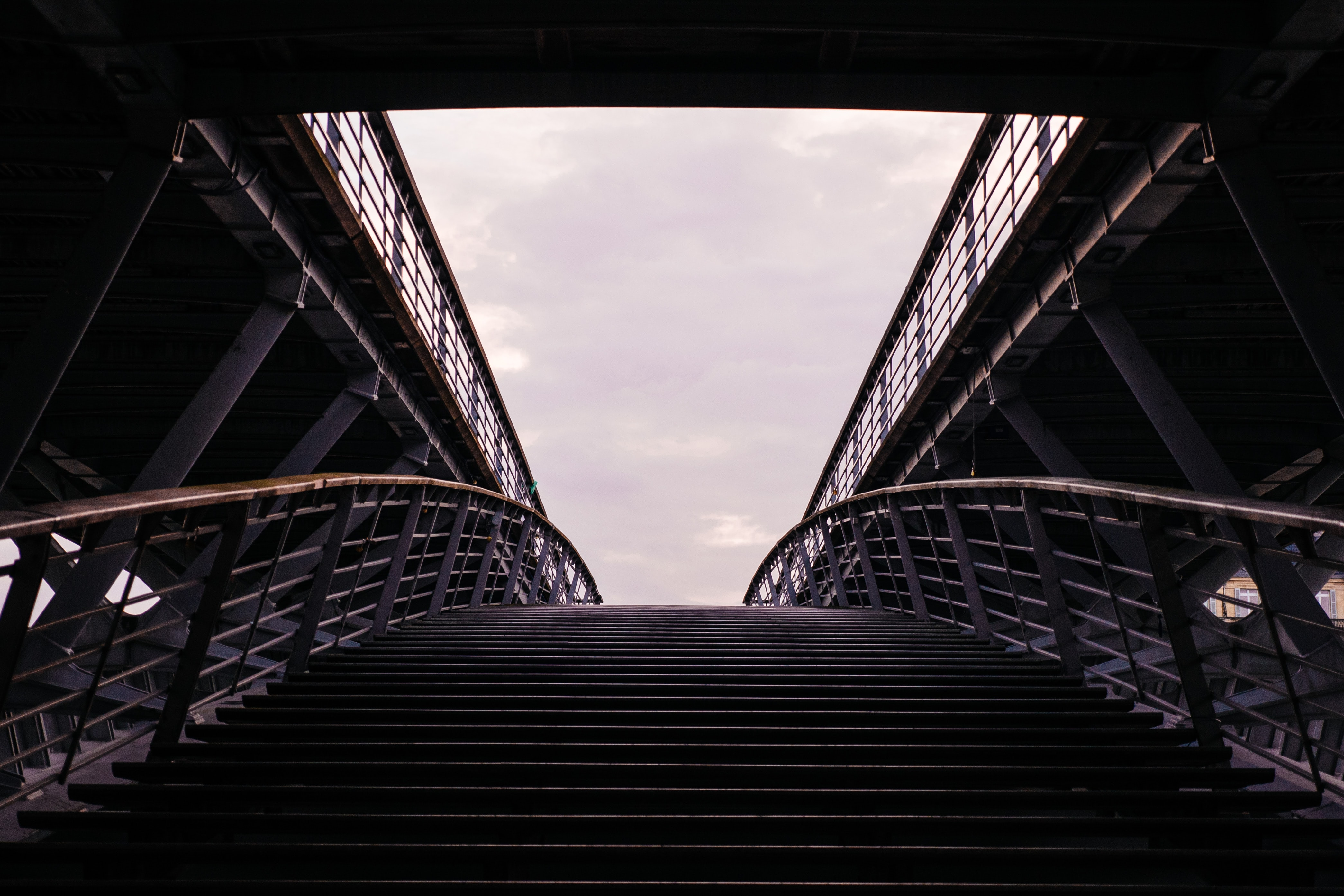 A symmetrical shot of stairs leading up to a bridge