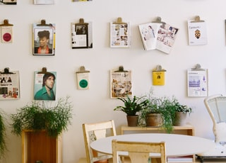 magazines hanged on wall near round beige wooden table