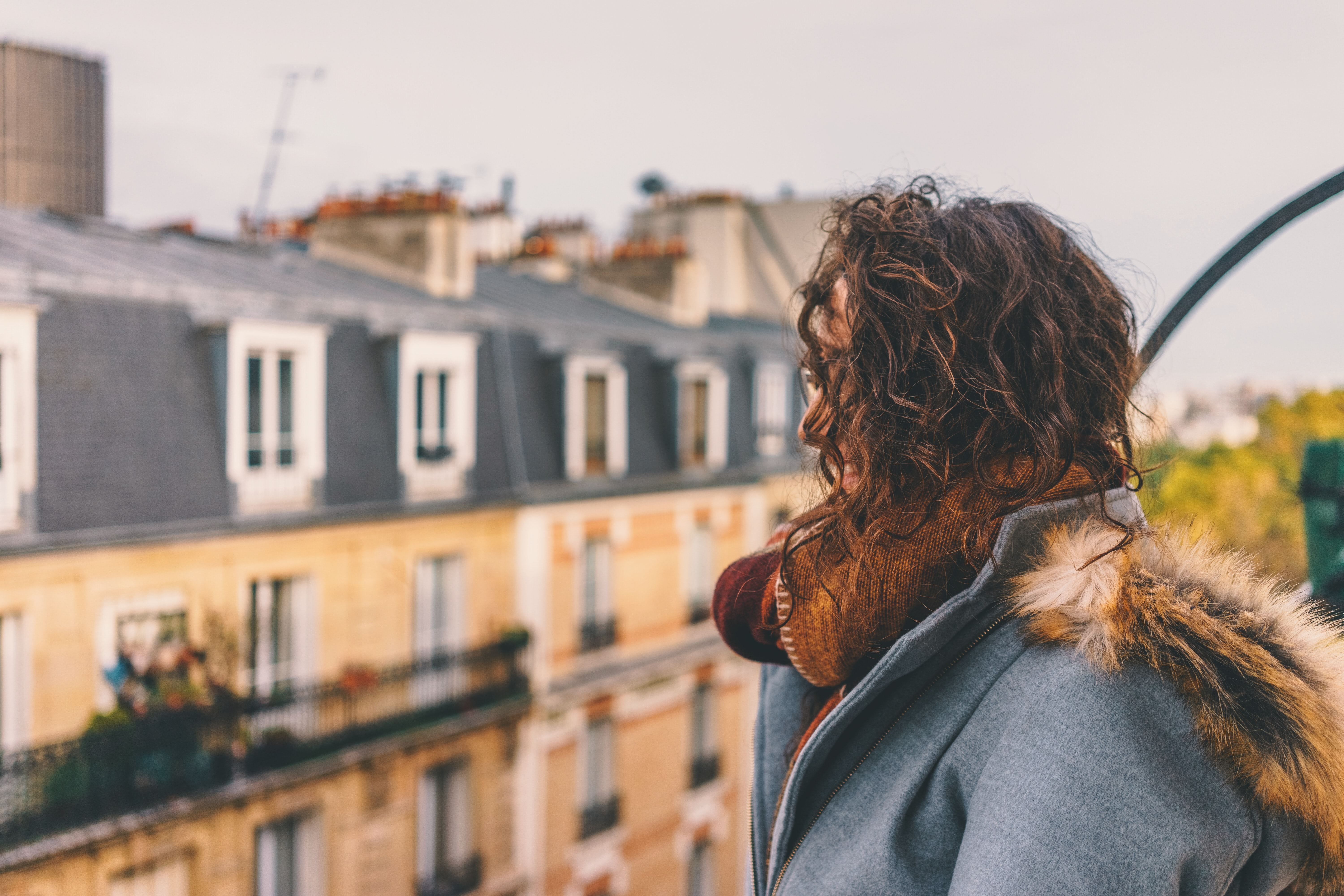 A woman wearing a jacket and scarf with Parisian architecture in the background.