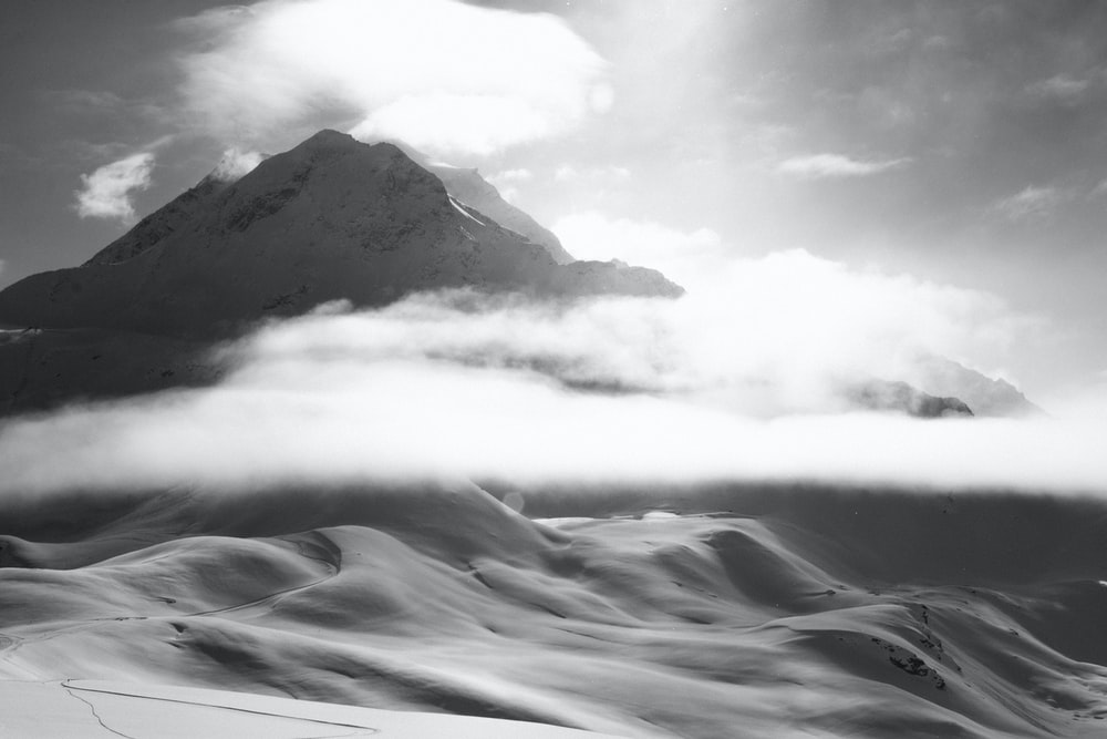 grayscale photo of mountain covered by fogs