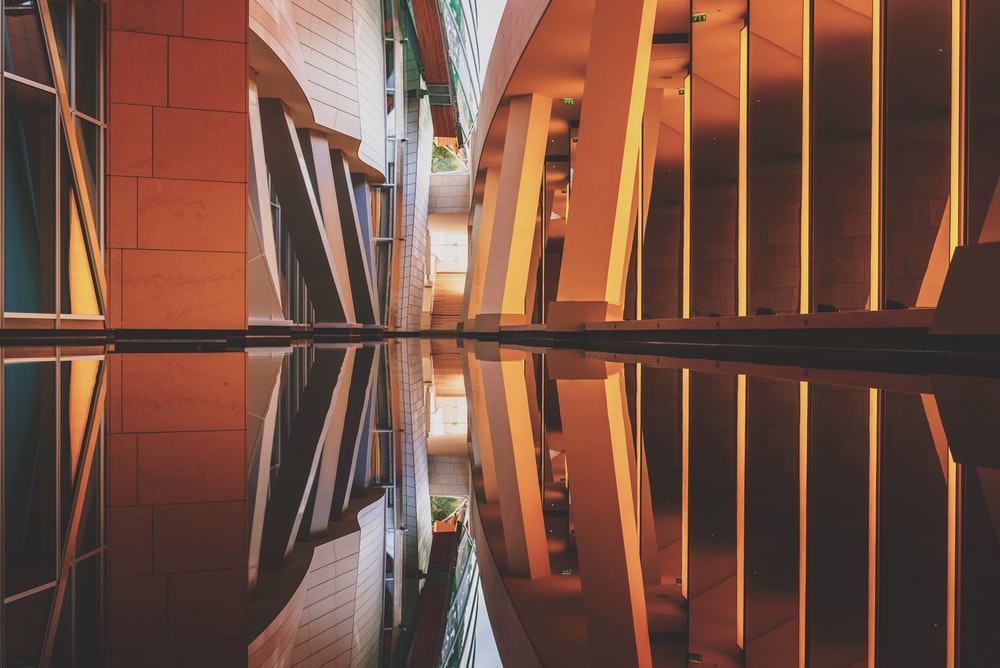 brown and black narrow building with reflection on the water photography