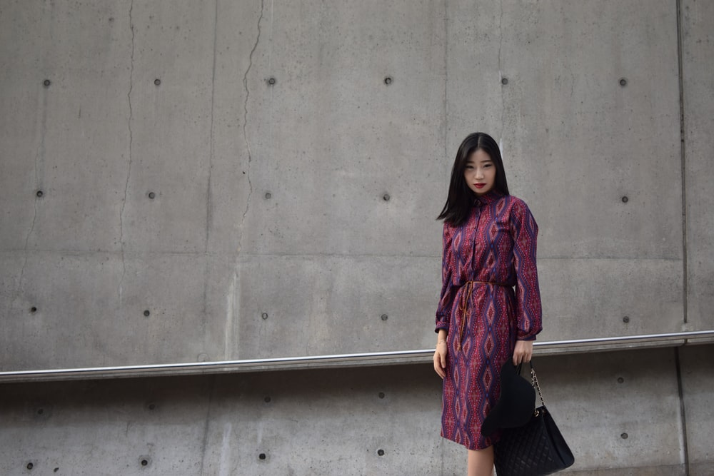 woman holding bag standing beside wall