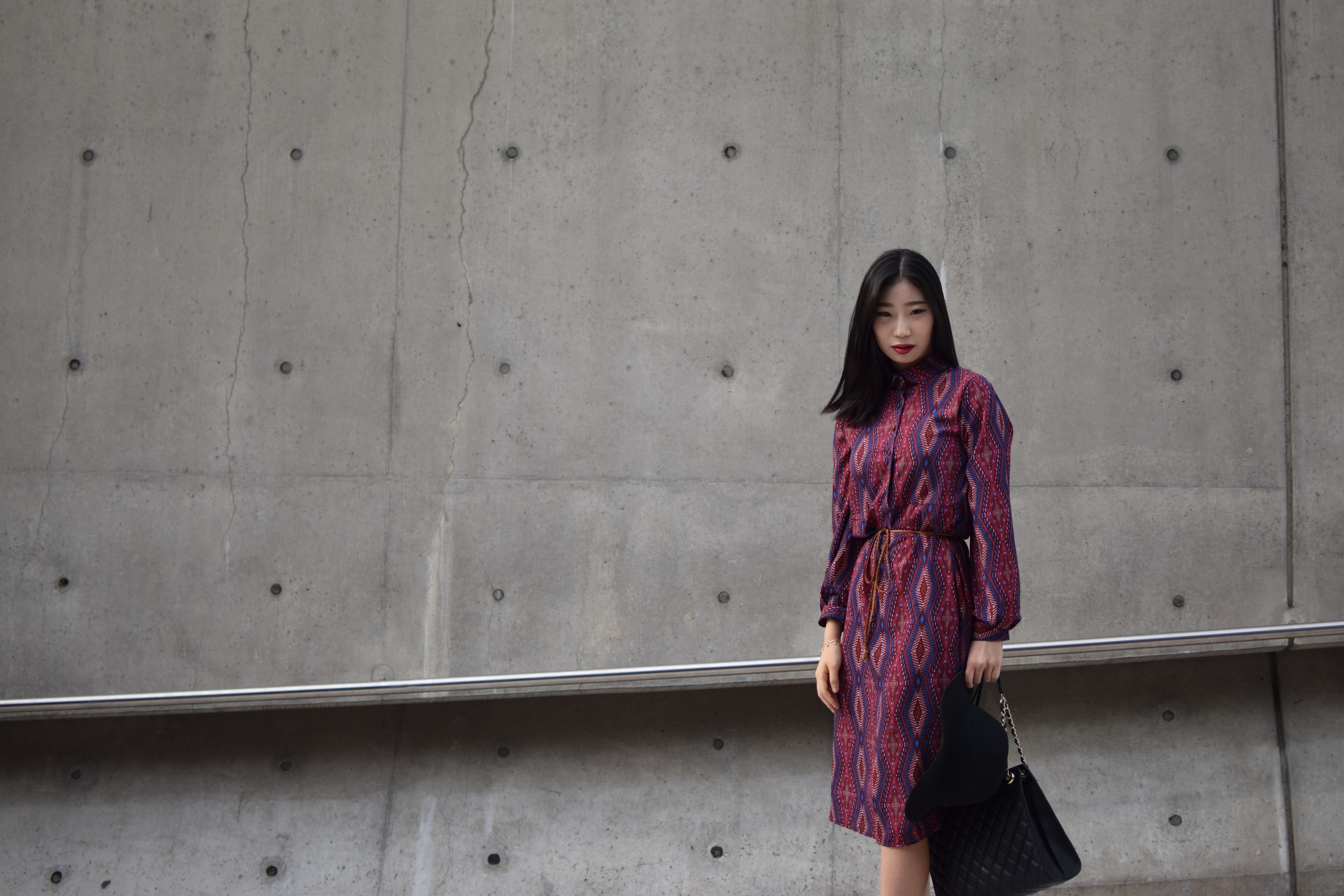 A woman in a fashionable pink-and-purple printed dress with a black purse before a stone wall