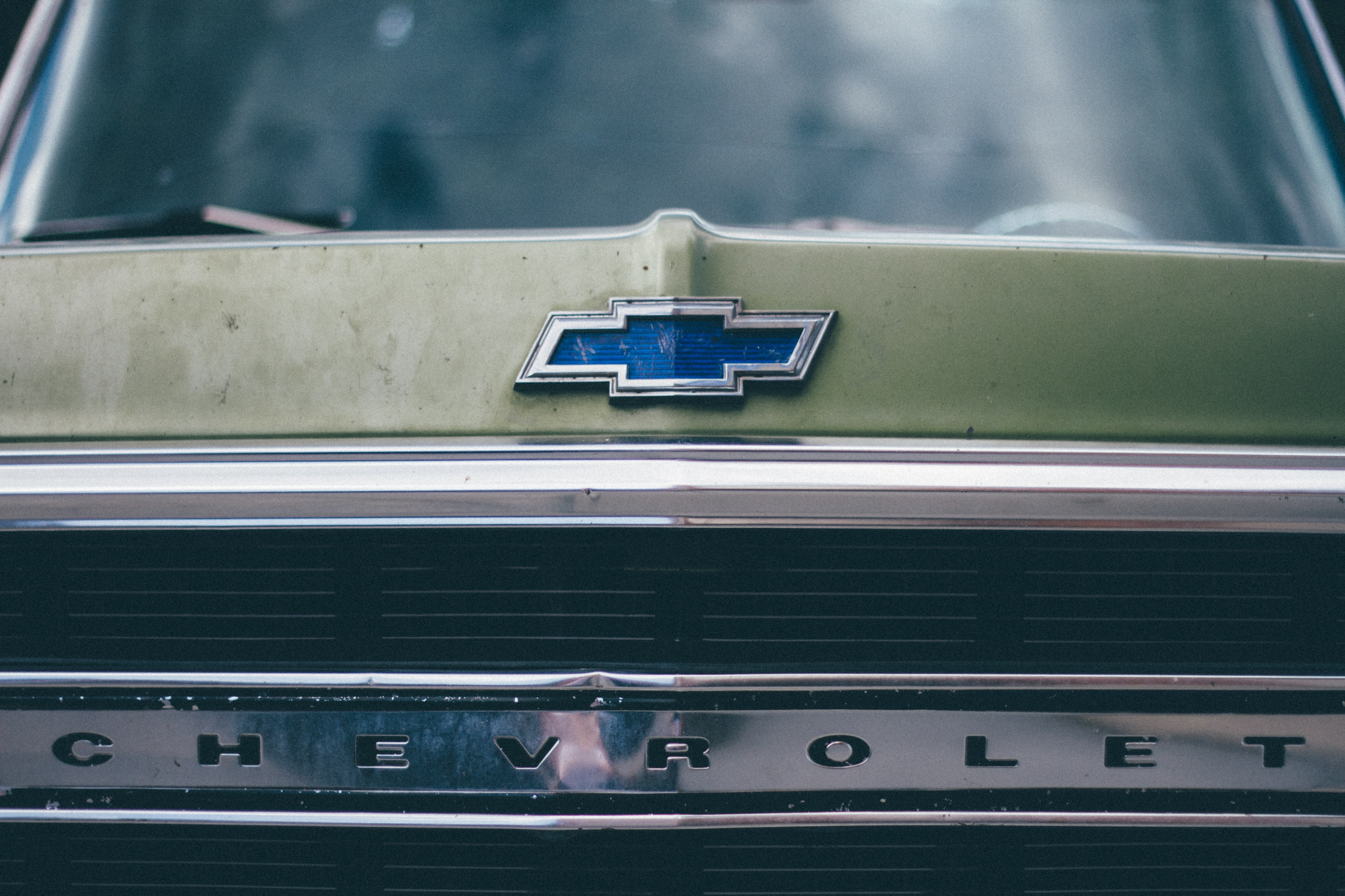 Macro shot of a vintage Chevrolet truck's grille and emblem.