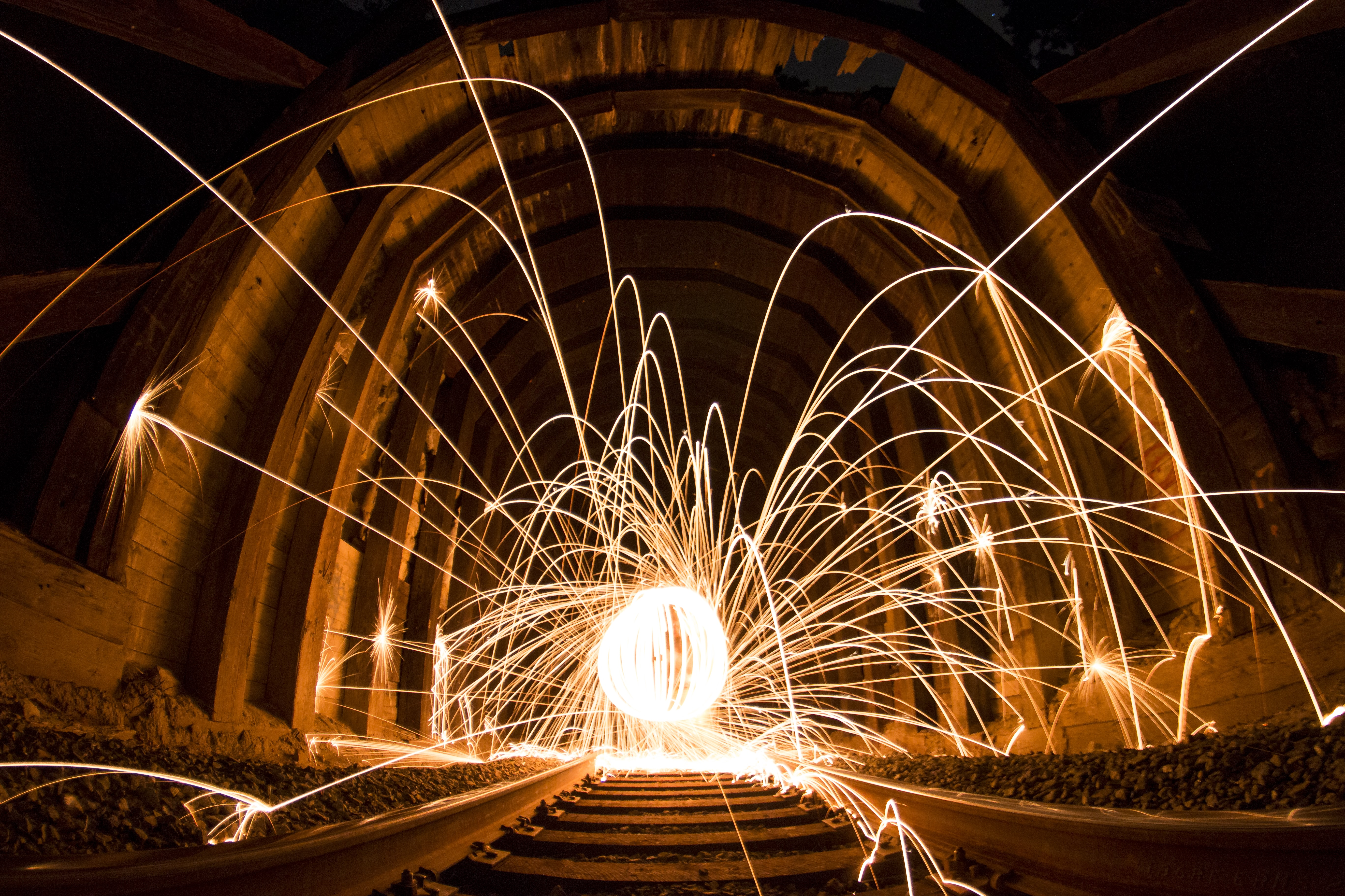 A long exposure shot of steel wool light trails in an Ironwood train tunnel