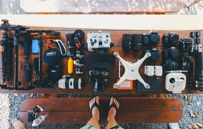 person standing near black and white quadcopter drone near cameras on brown wooden table gopro teams background
