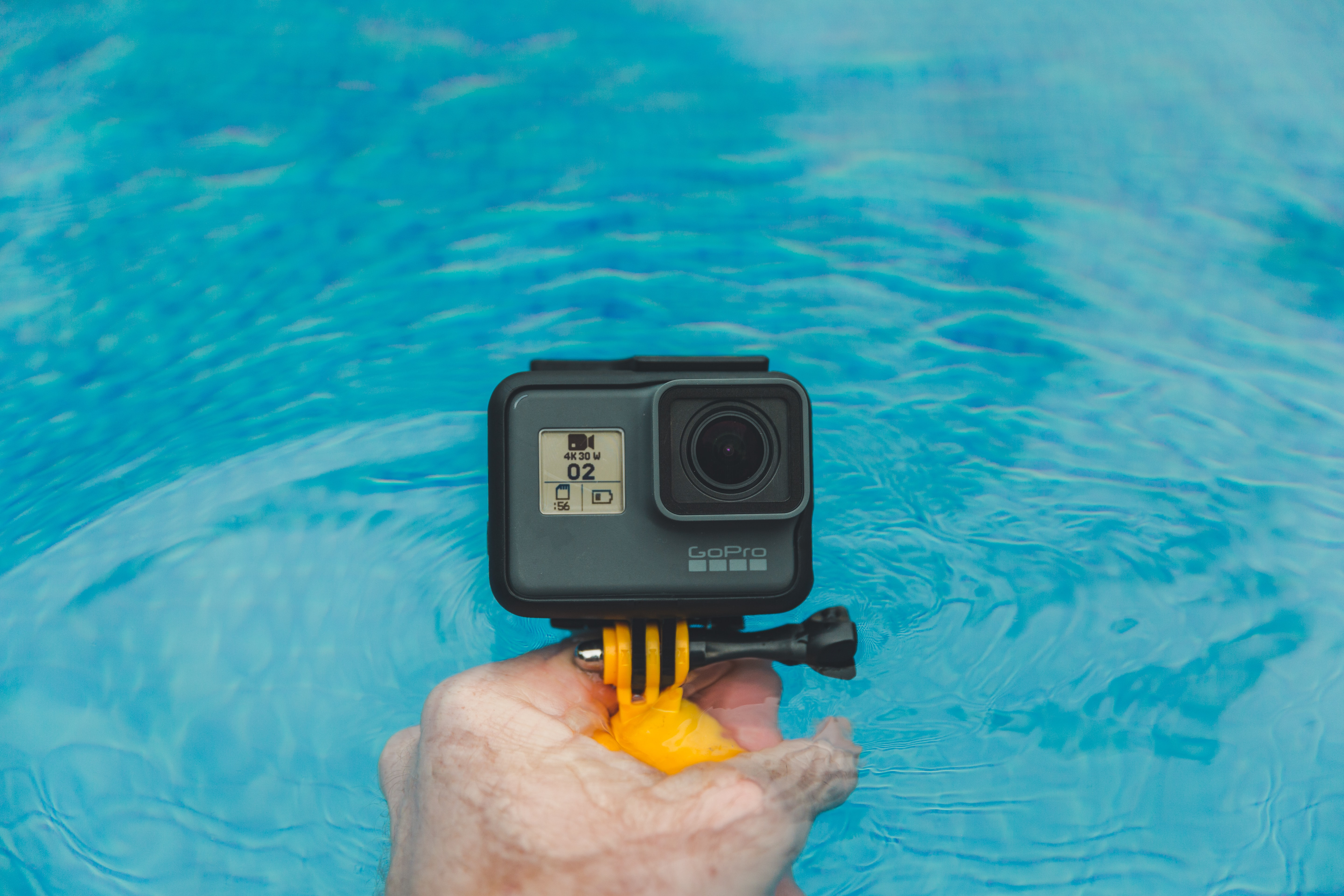 A GoPro camera is being held over the water surface.