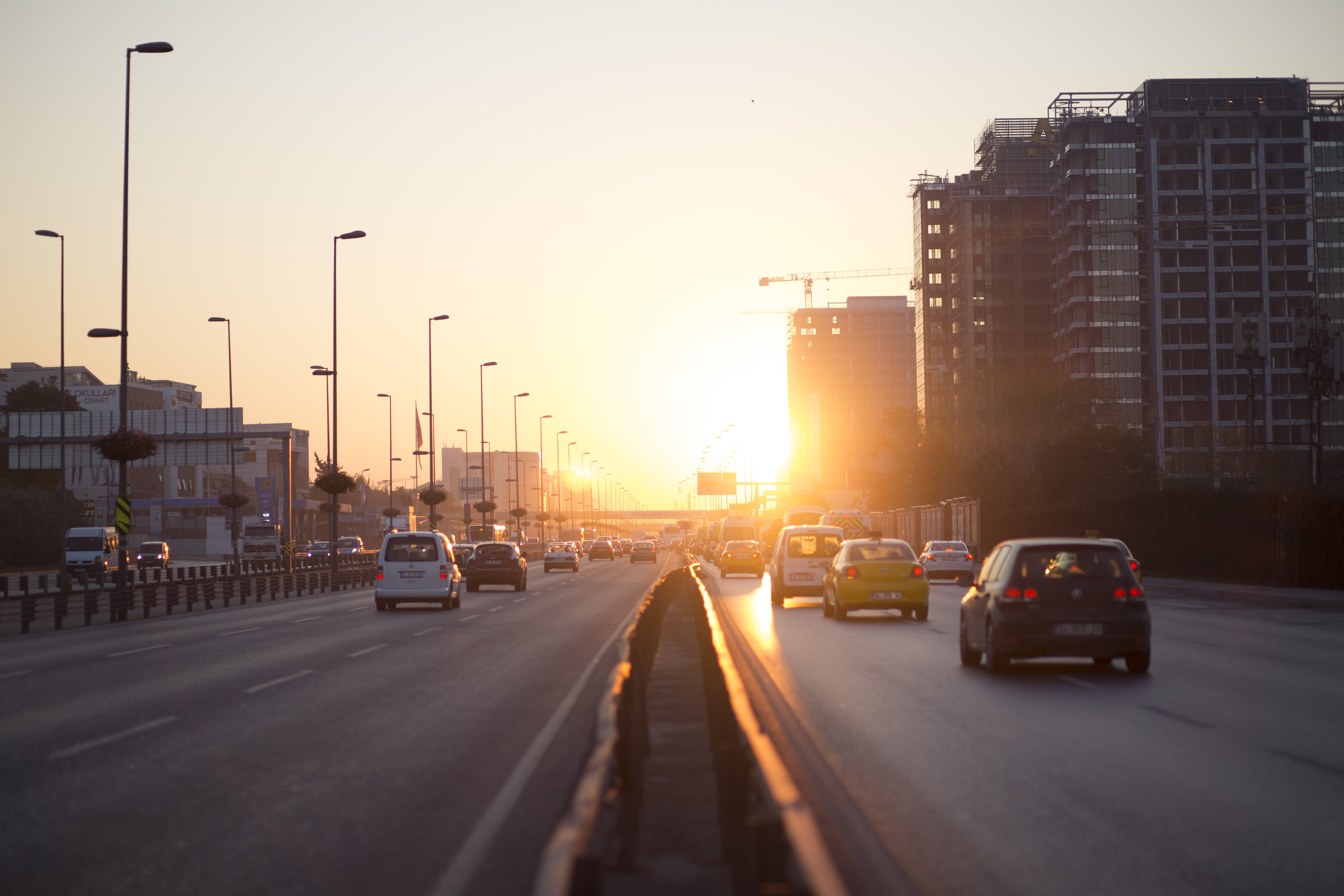 vehicles on highway near buildings during golden hour