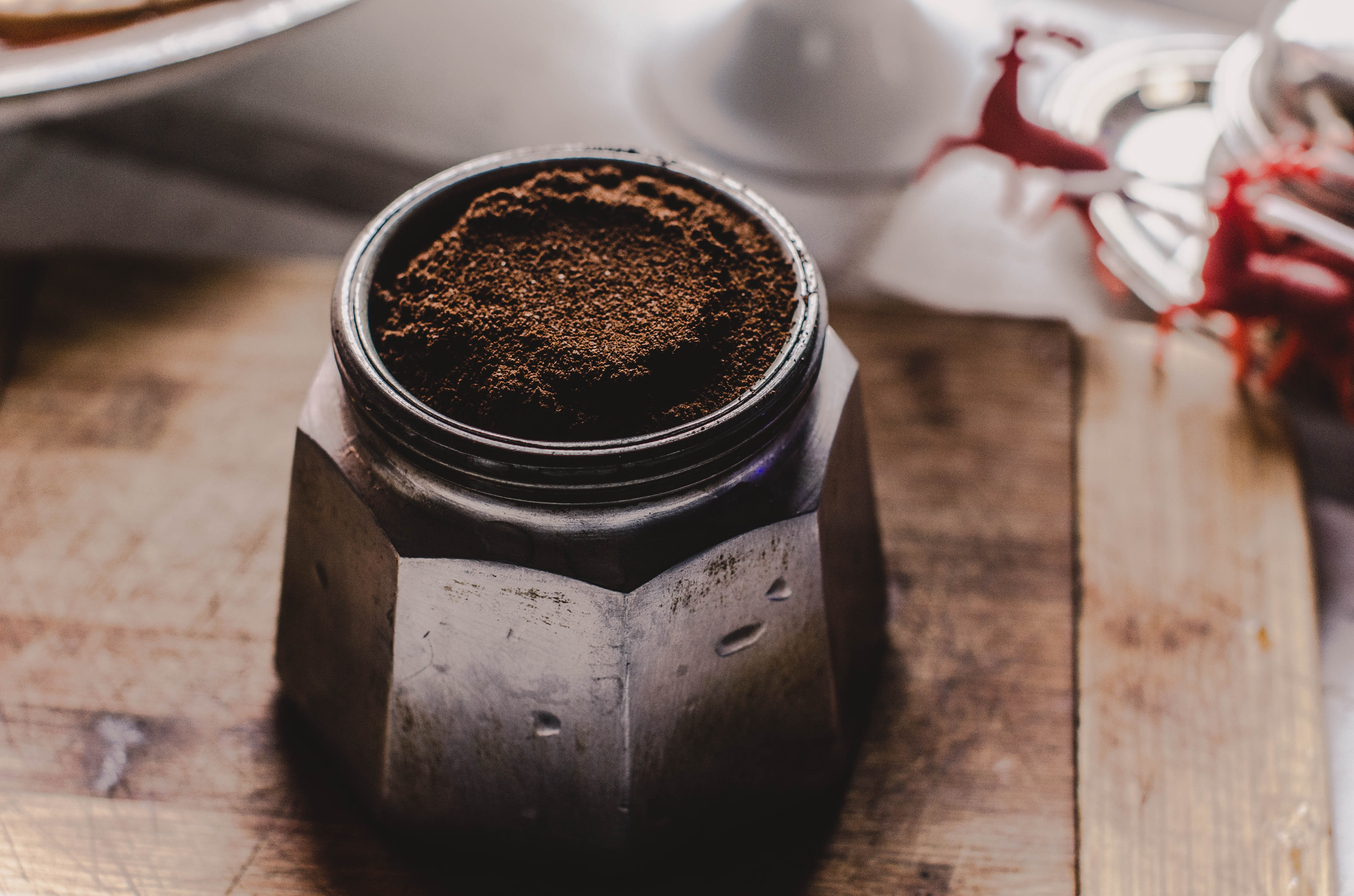 A close up look at coffee grounds in a container sitting on top of a wood board