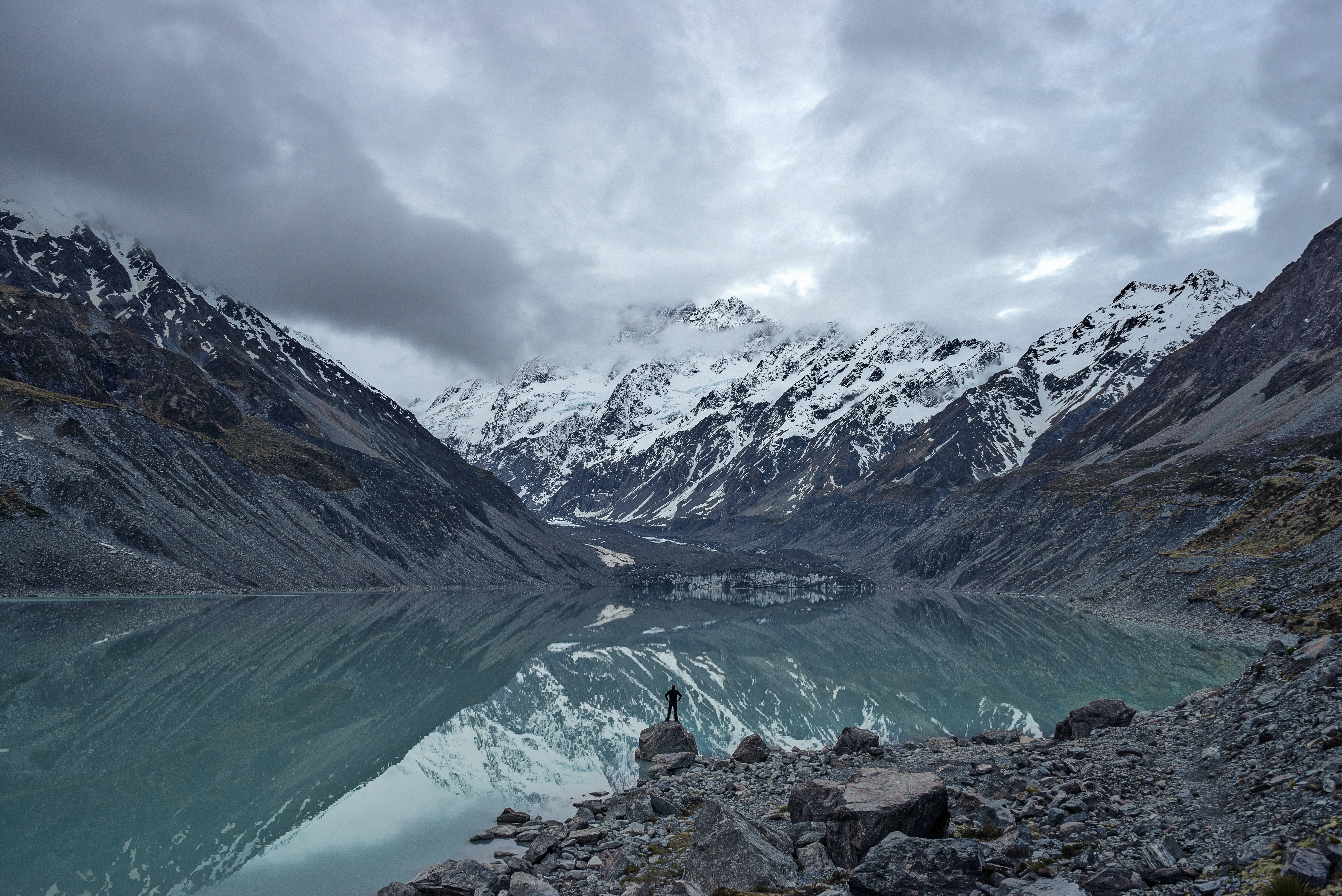 Snowy mountains are reflected in the water of Hooker Lake