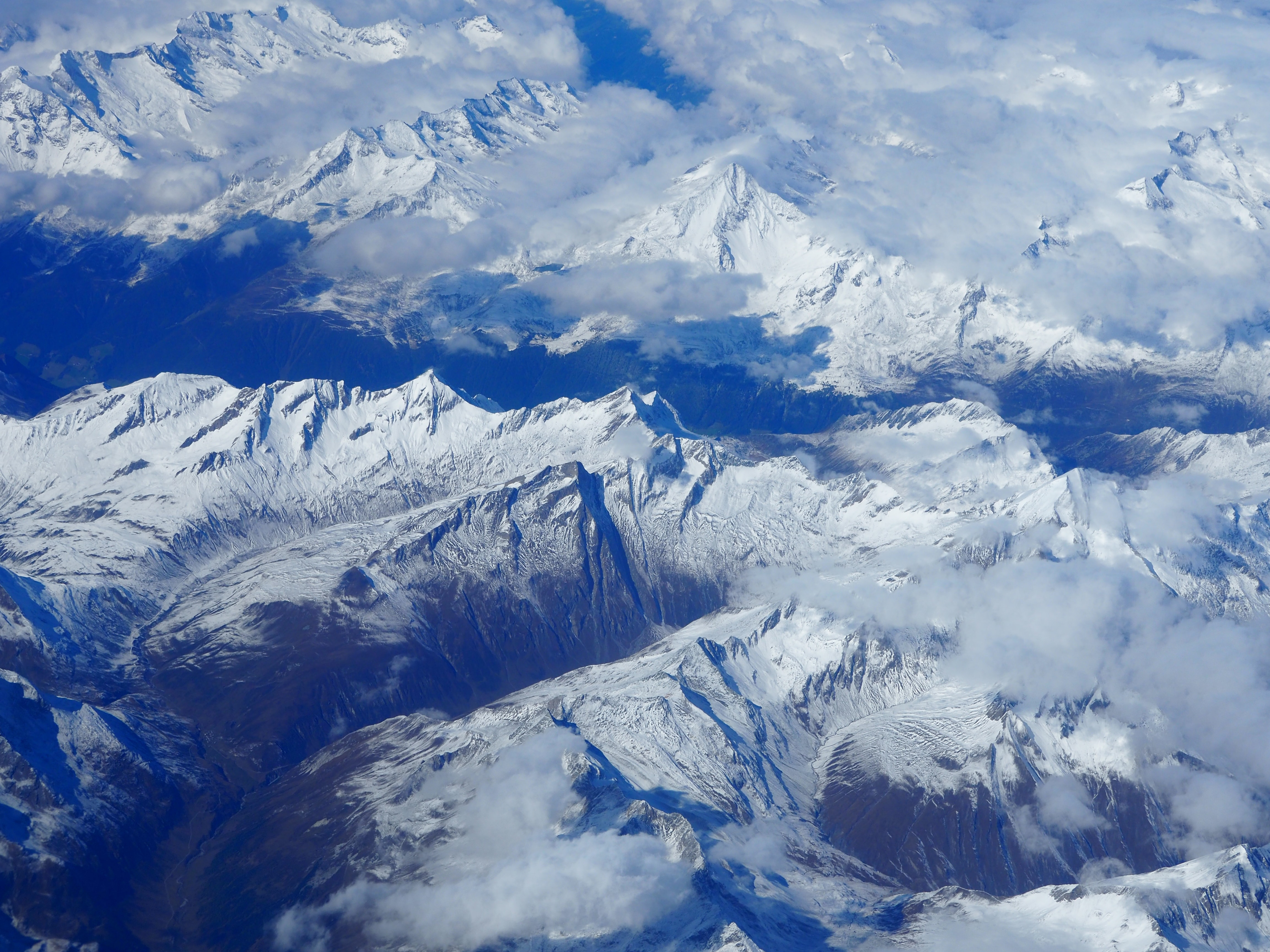 An aerial shot of an Alpine mountain range under a cover of clouds