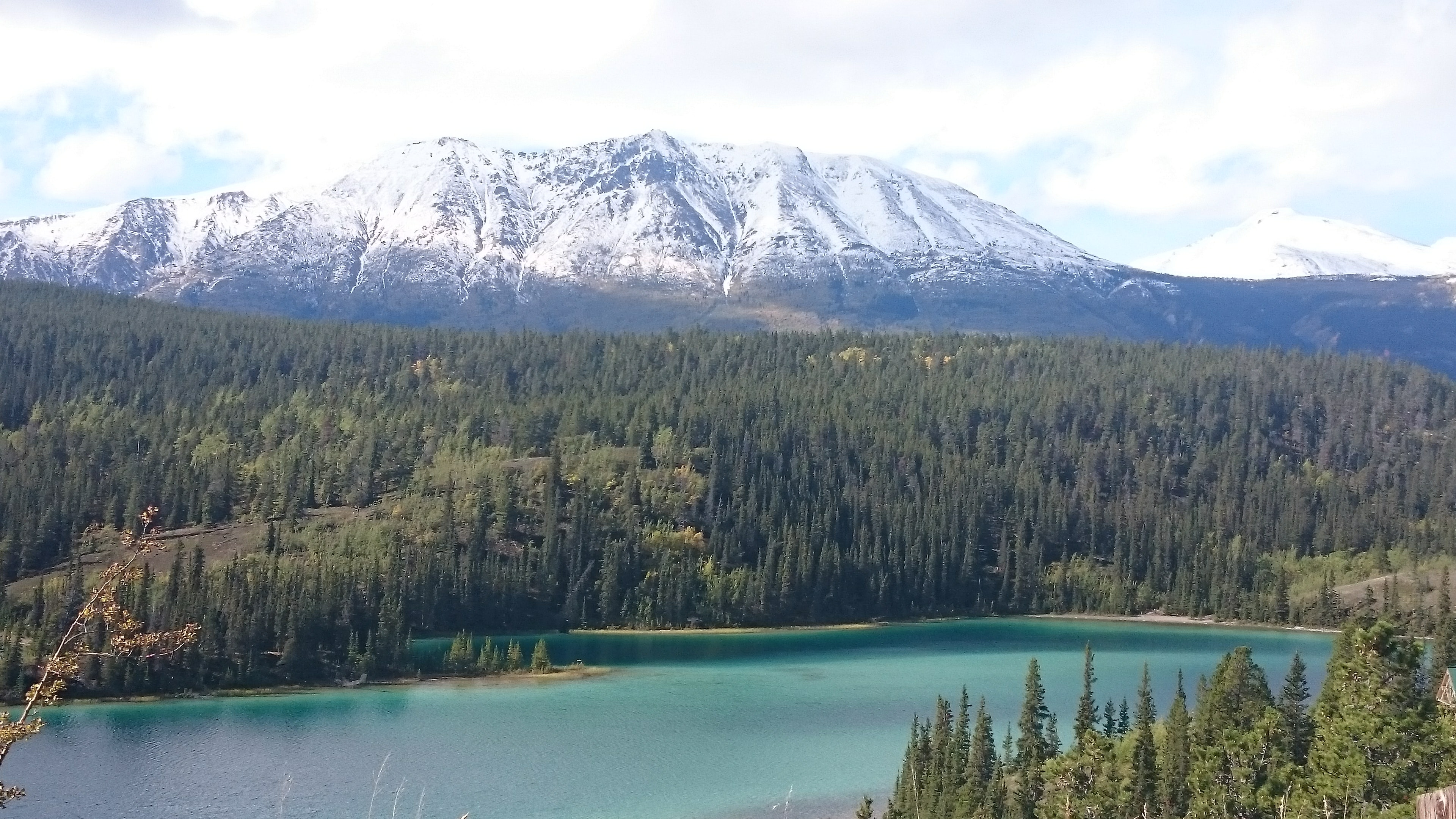 Snowy table-top mountain towering over Emerald Lake in Yukon