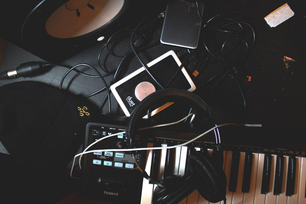 flat-lay photo of headphones, MIDI keyboard, and speaker on black surface