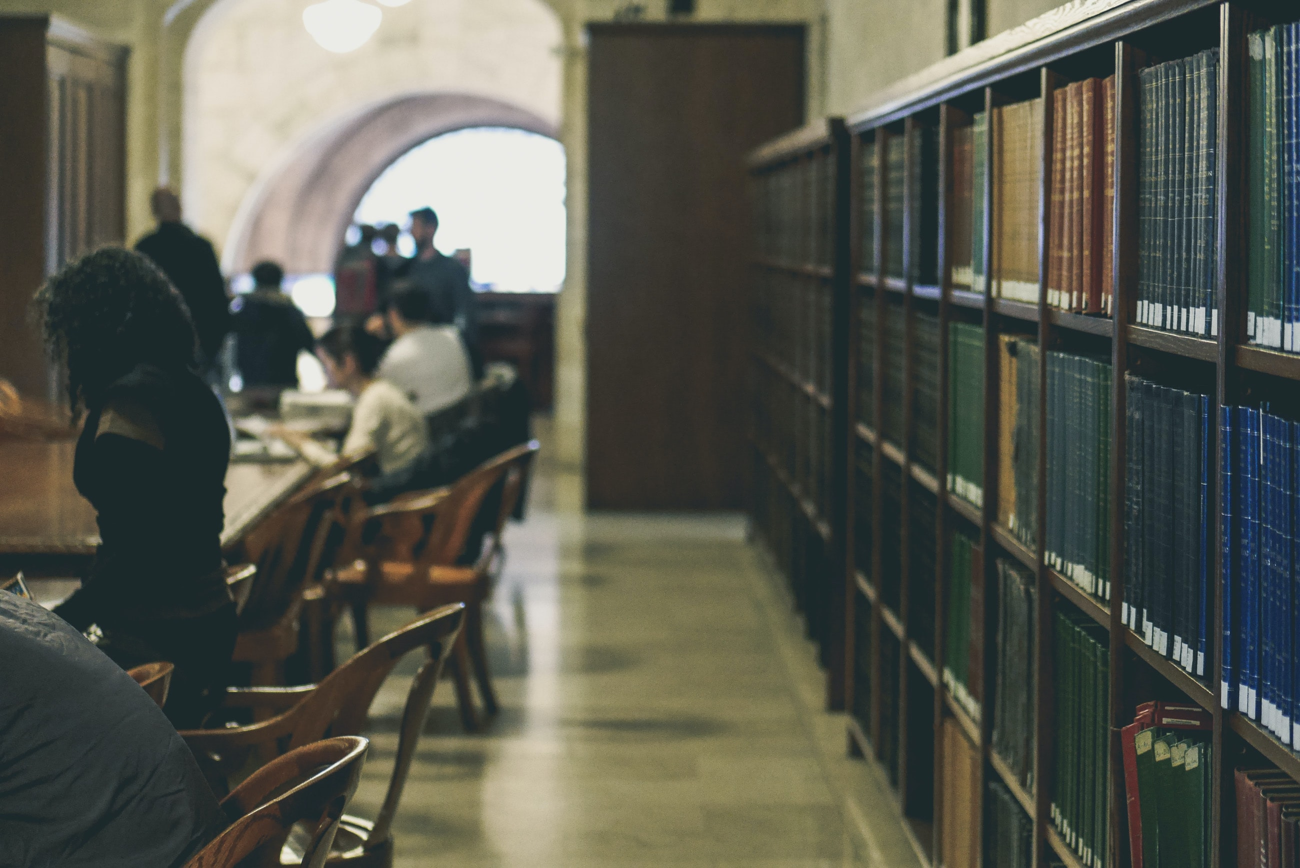 New York Public Library with library users and books on the bookshelves.
