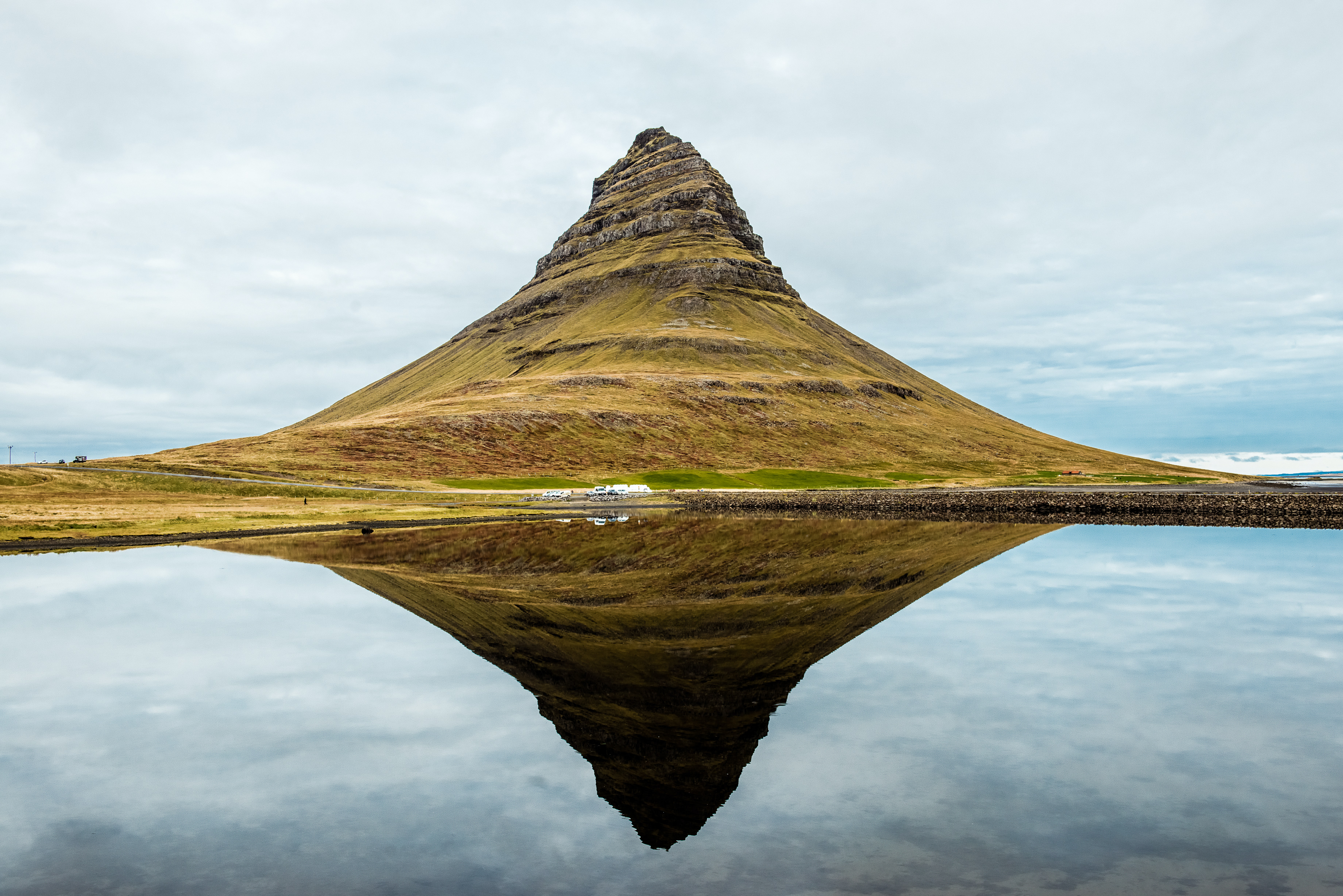 A free-standing mountain reflected in the clear surface of a lake