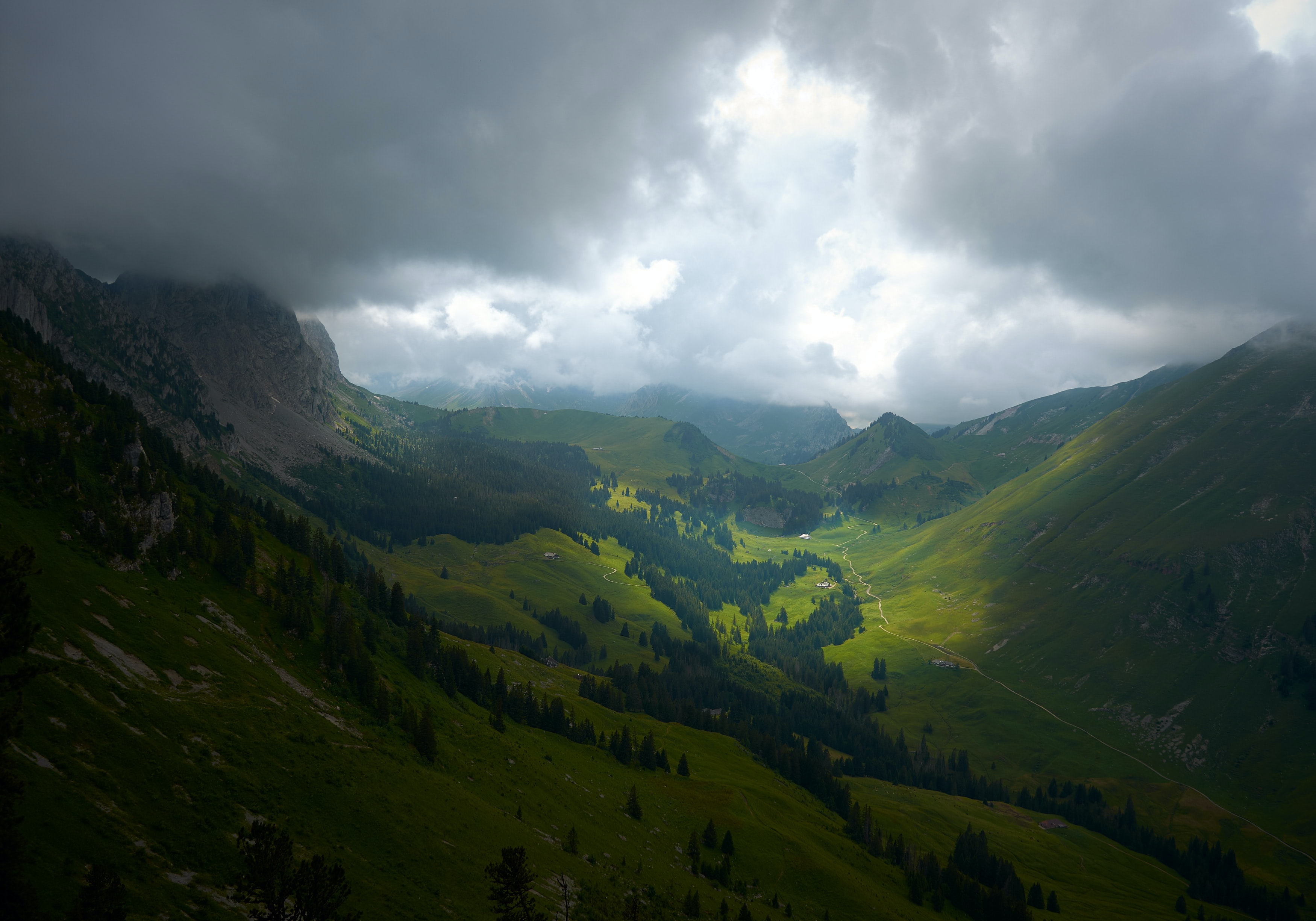 Sun shining through the thick clouds illuminates the bottom of a green valley