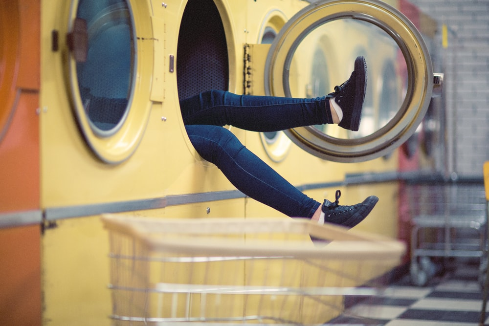 person wearing blue fitted jeans inside laundry machine during daytime