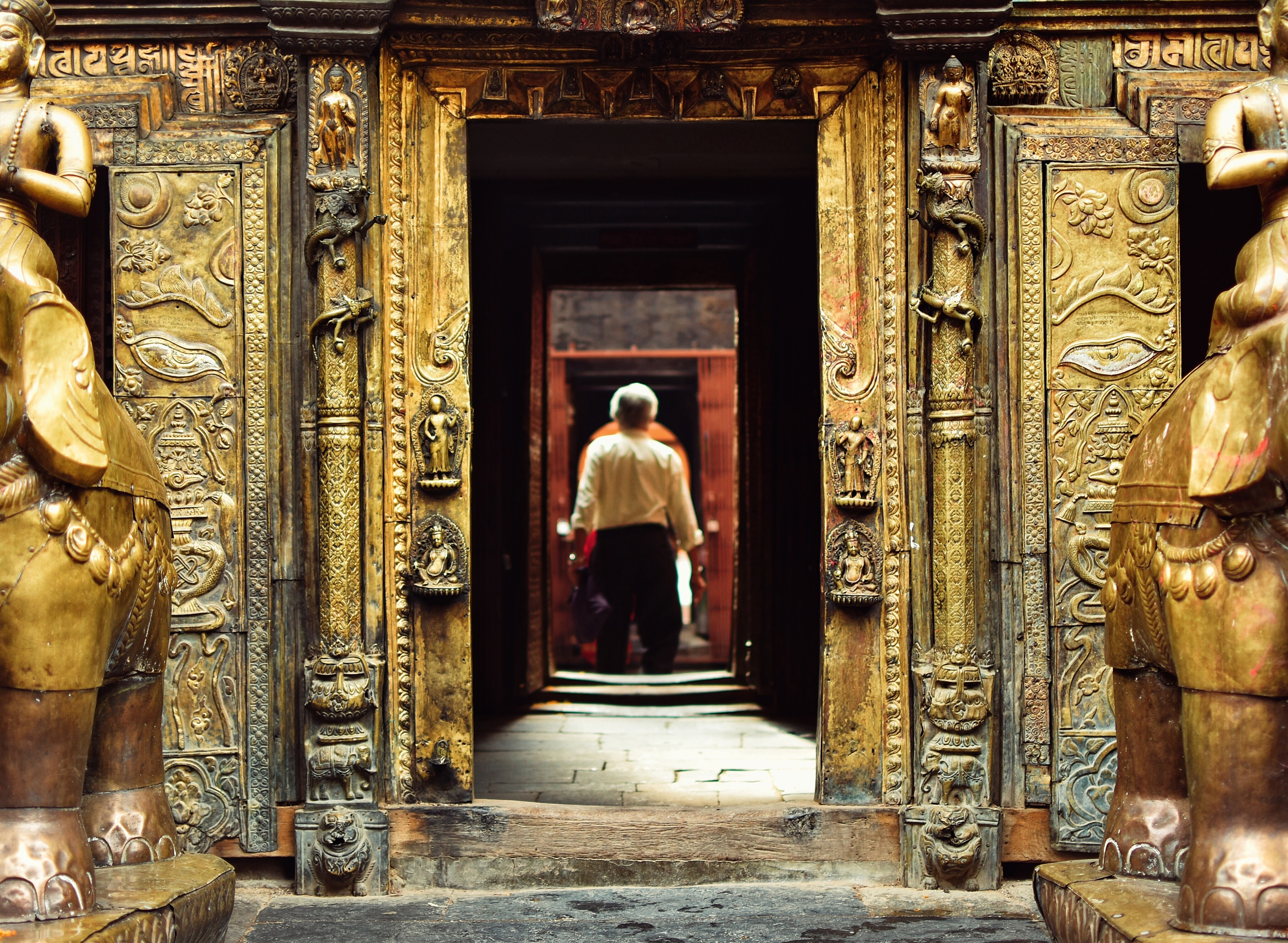 A man in a white shirt standing back to camera in the doorway of a Buddhist temple