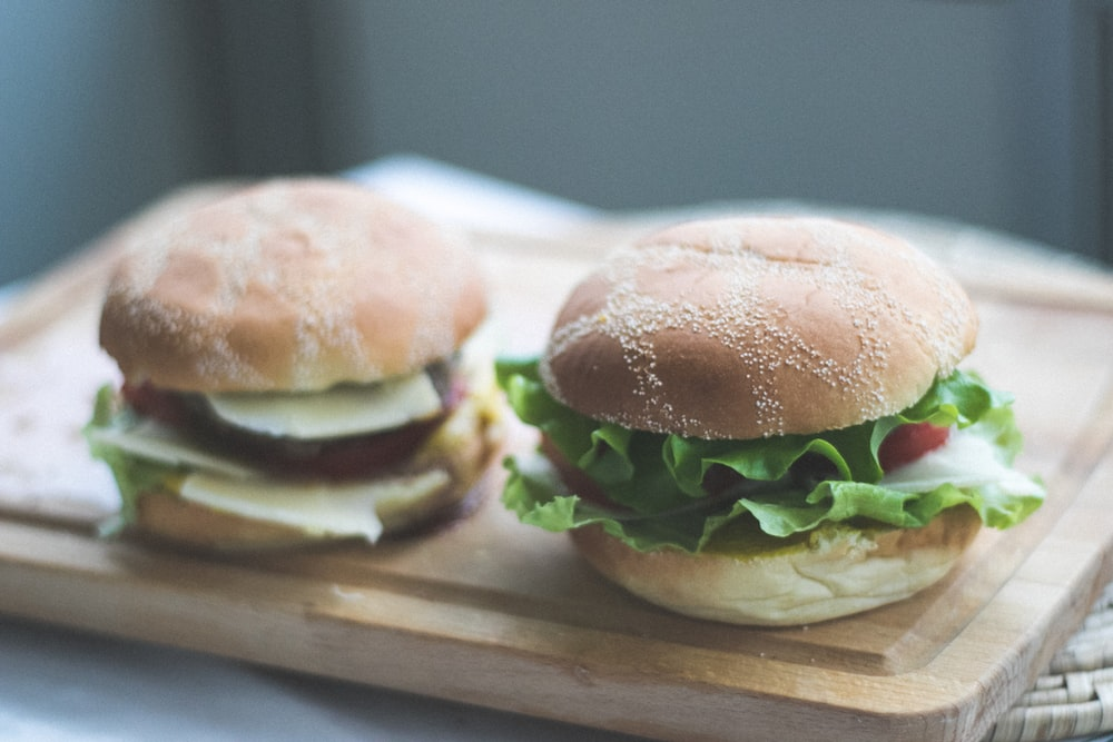 two burgers on brown wooden chopping board