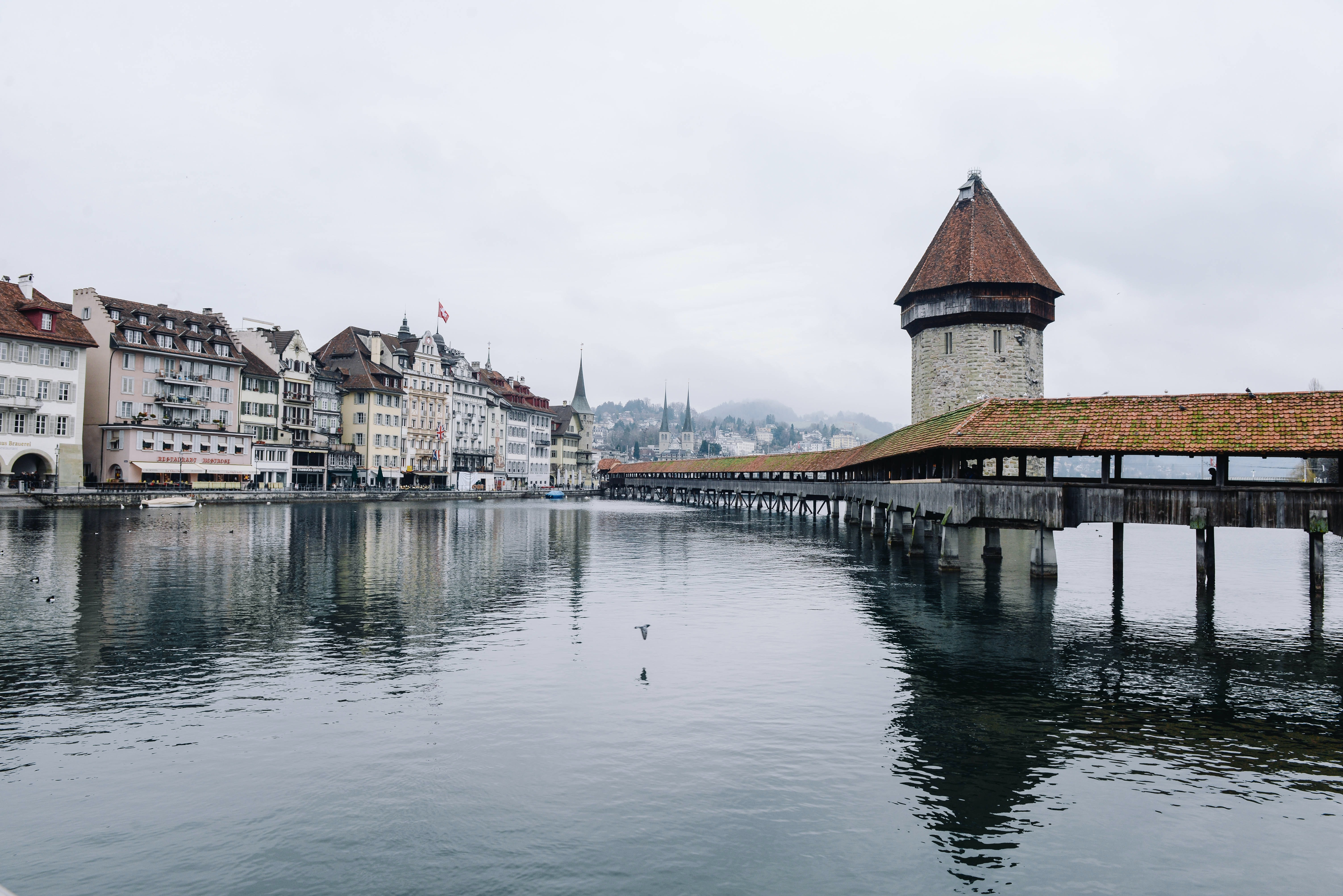 View of buildings and a bridge at the lakeside in Lucerne on a foggy day