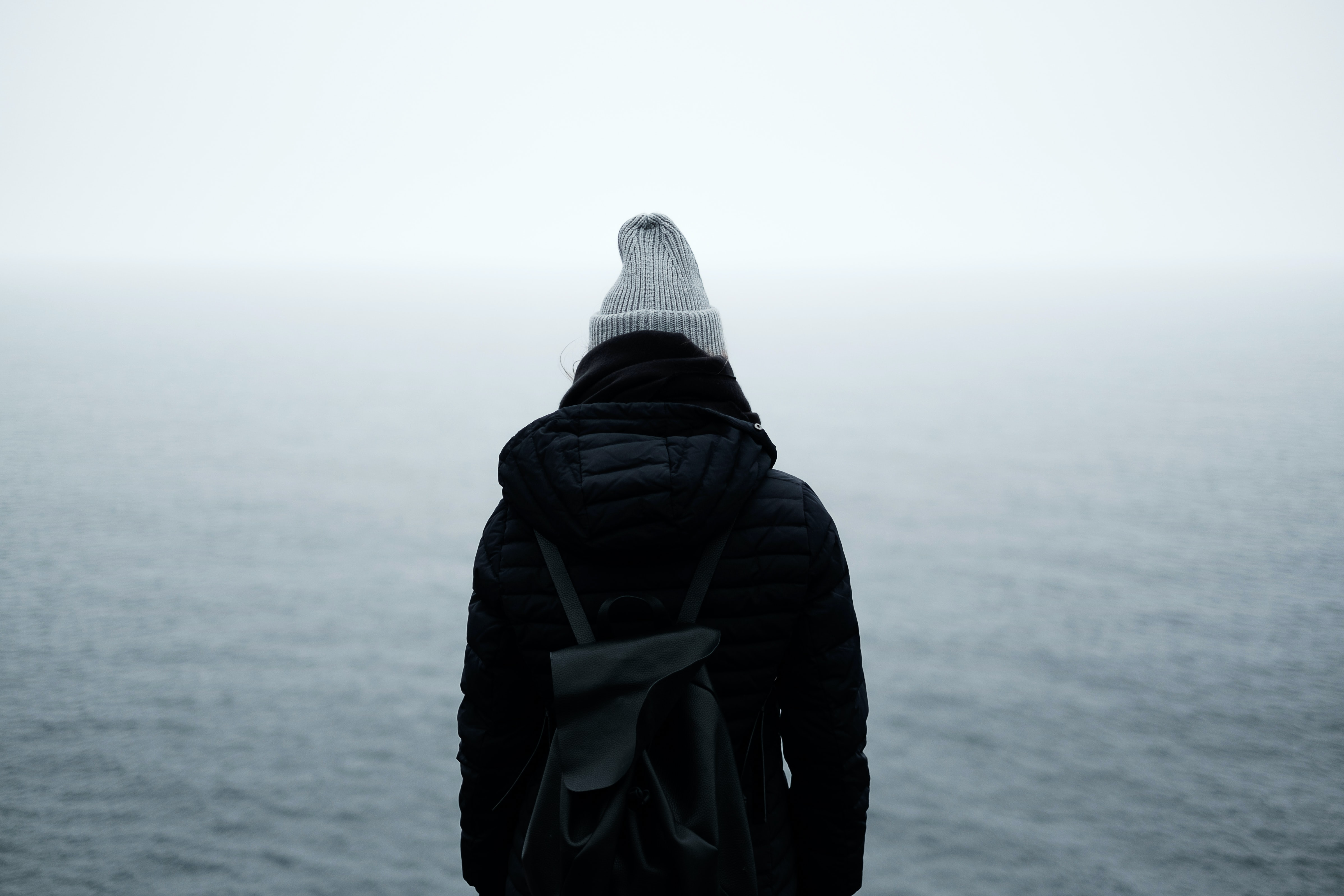 Person in winter wear with backpack watches misty water in Cape Spear