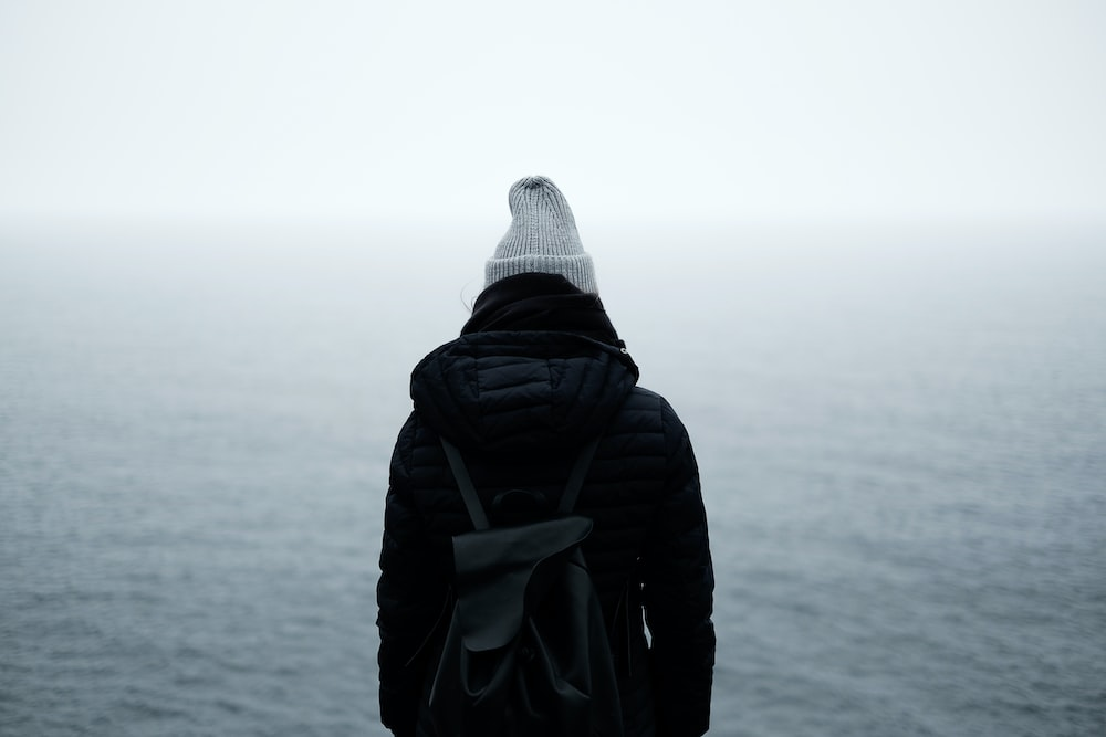 person wearing black jacket standing in front of the ocean